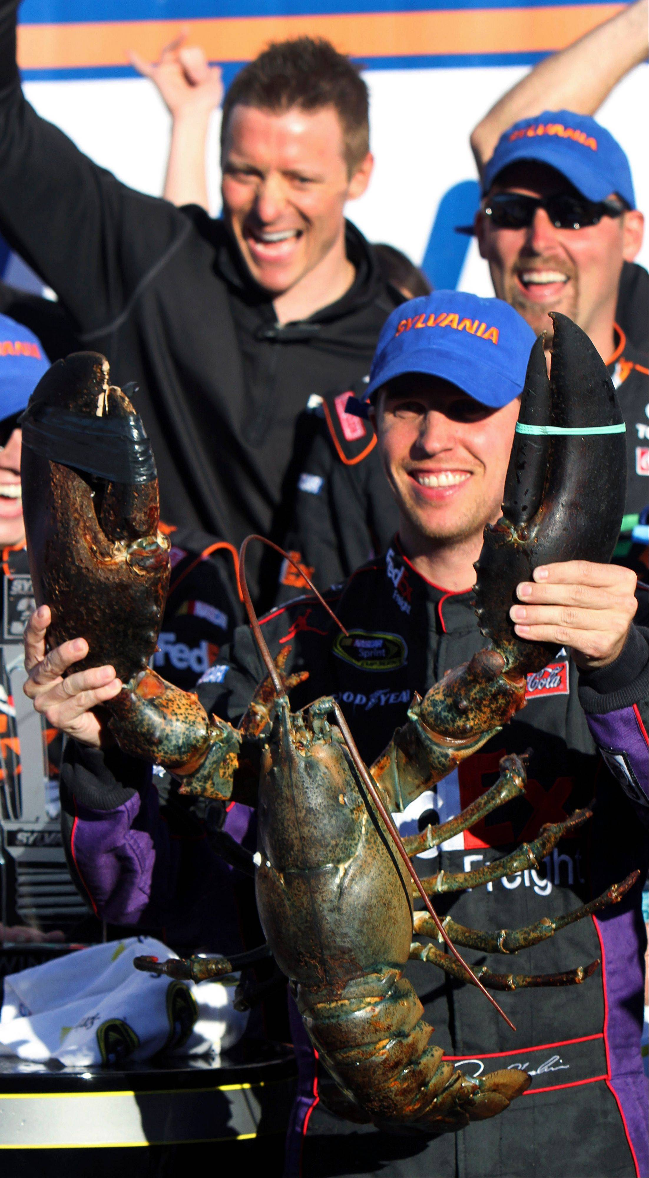 Denny Hamlin holds up a lobster in victory lane Sunday after winning the NASCAR Sprint Cup Series auto race at New Hampshire Motor Speedway in Loudon, N.H.