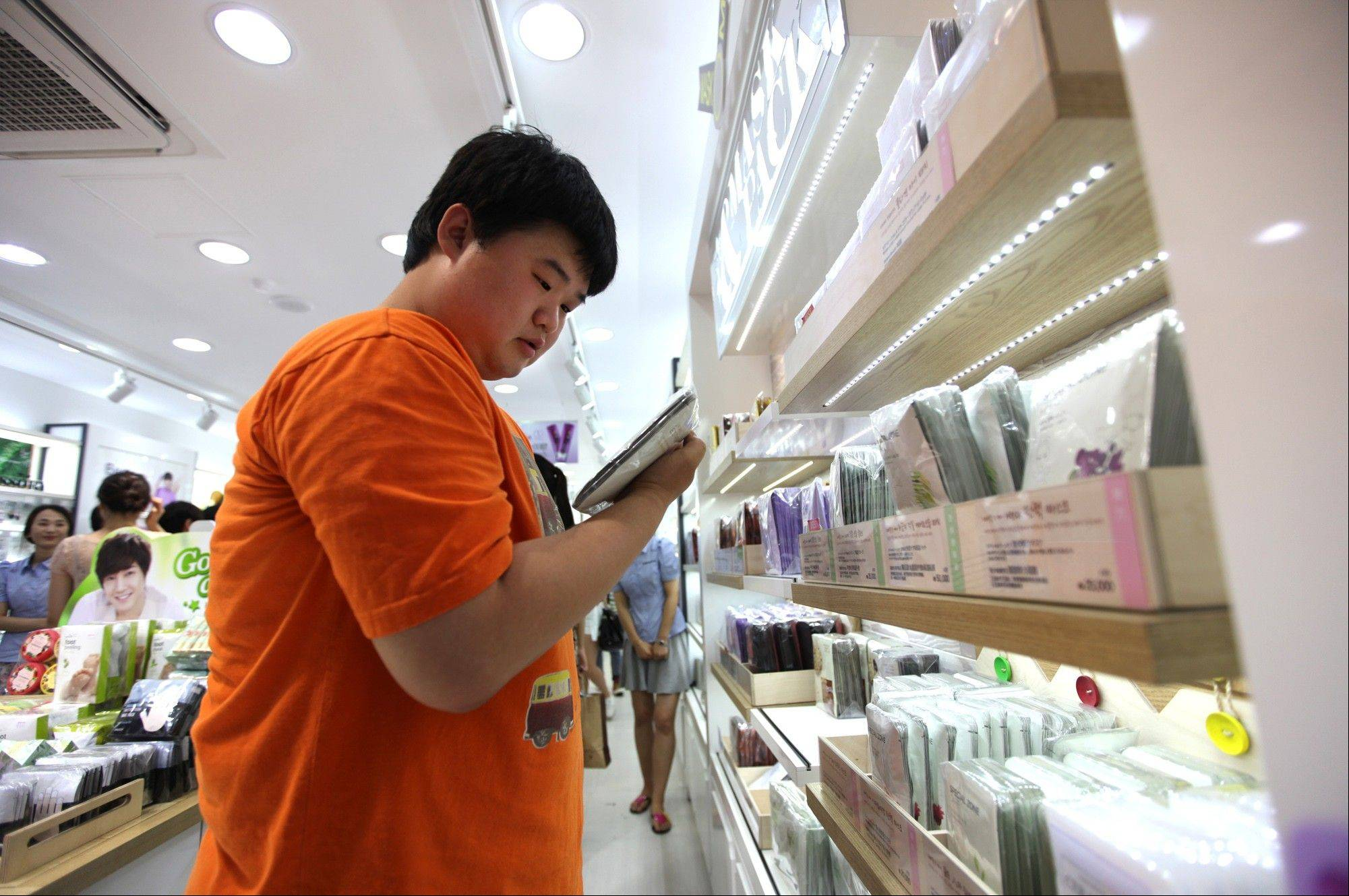 "Cho Gil-nam, a 27-year-old insurance fraud investigator, shops for skin care and makeup products at a cosmetics store in Seoul, South Korea. The metamorphosis of South Korean men from macho to makeup over the last decade or so can be partly explained by fierce competition for jobs, advancement and romance in a society where, as a popular catchphrase puts it, ""appearance is power."""