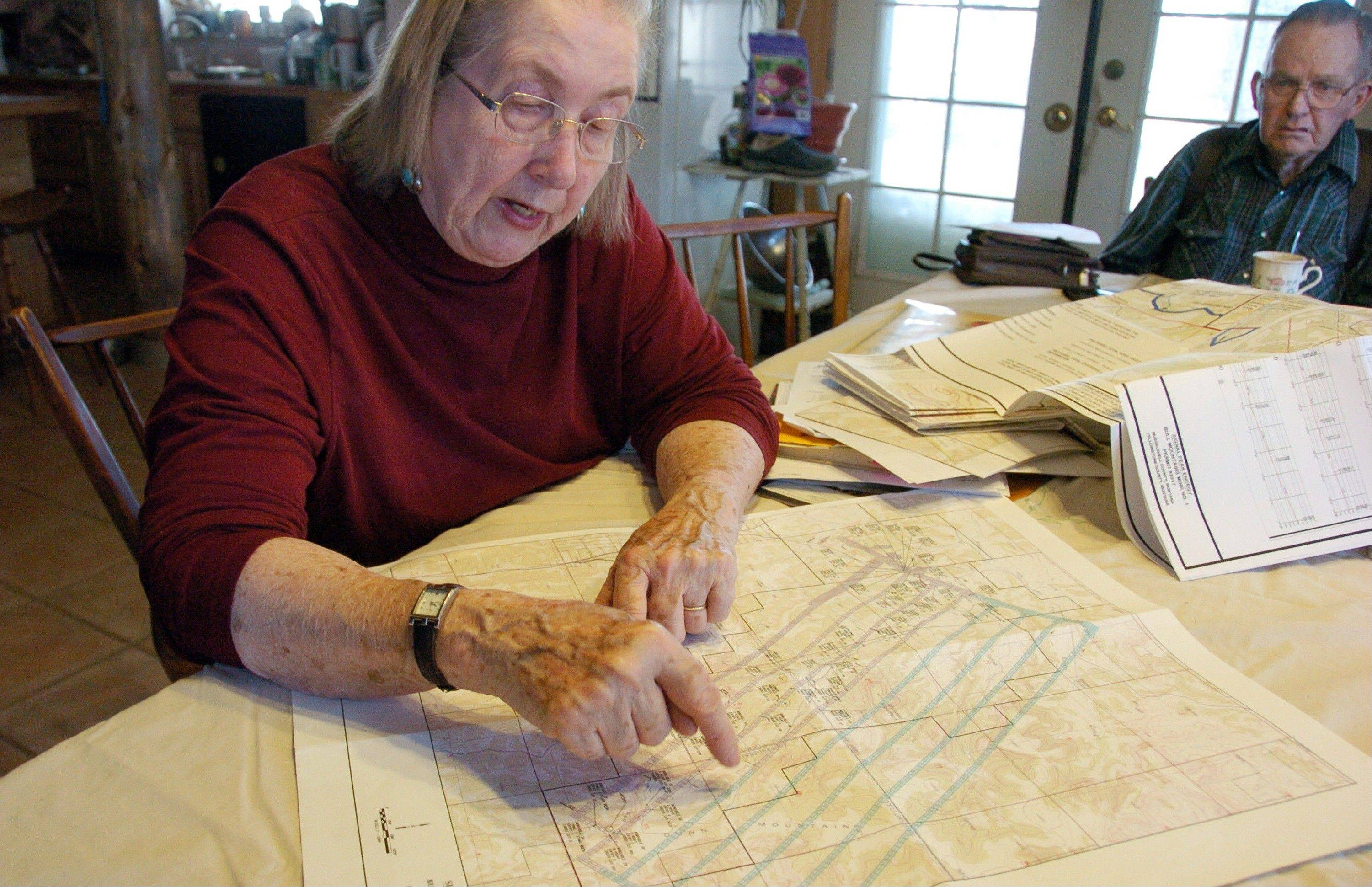 Ellen Pfister looks over a map depicting the Bull Mountain Mine that reaches beneath her ranch as husband Don Golder looks on from their house south of Roundup, Mont.