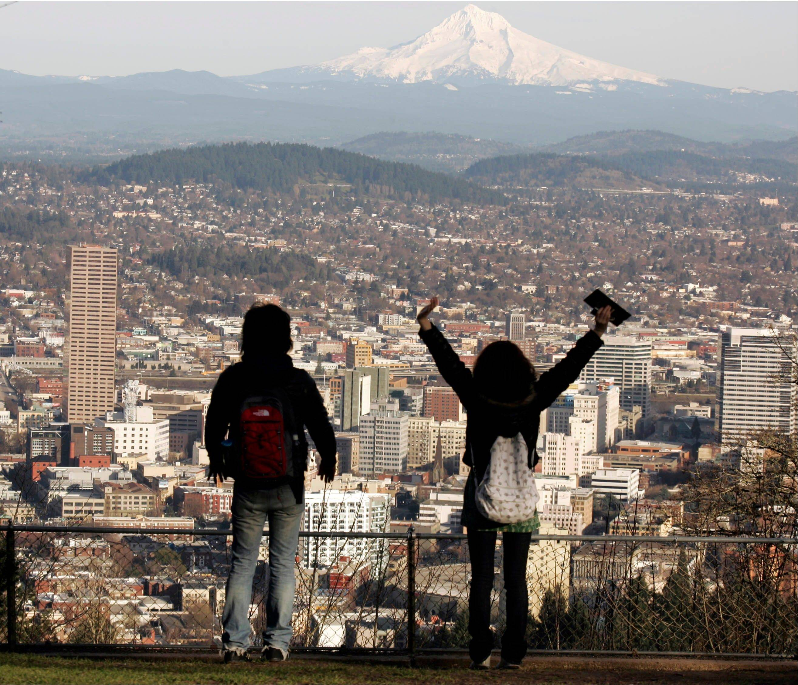 A young couple enjoy the view of Mount Hood looming over downtown Portland, Ore.