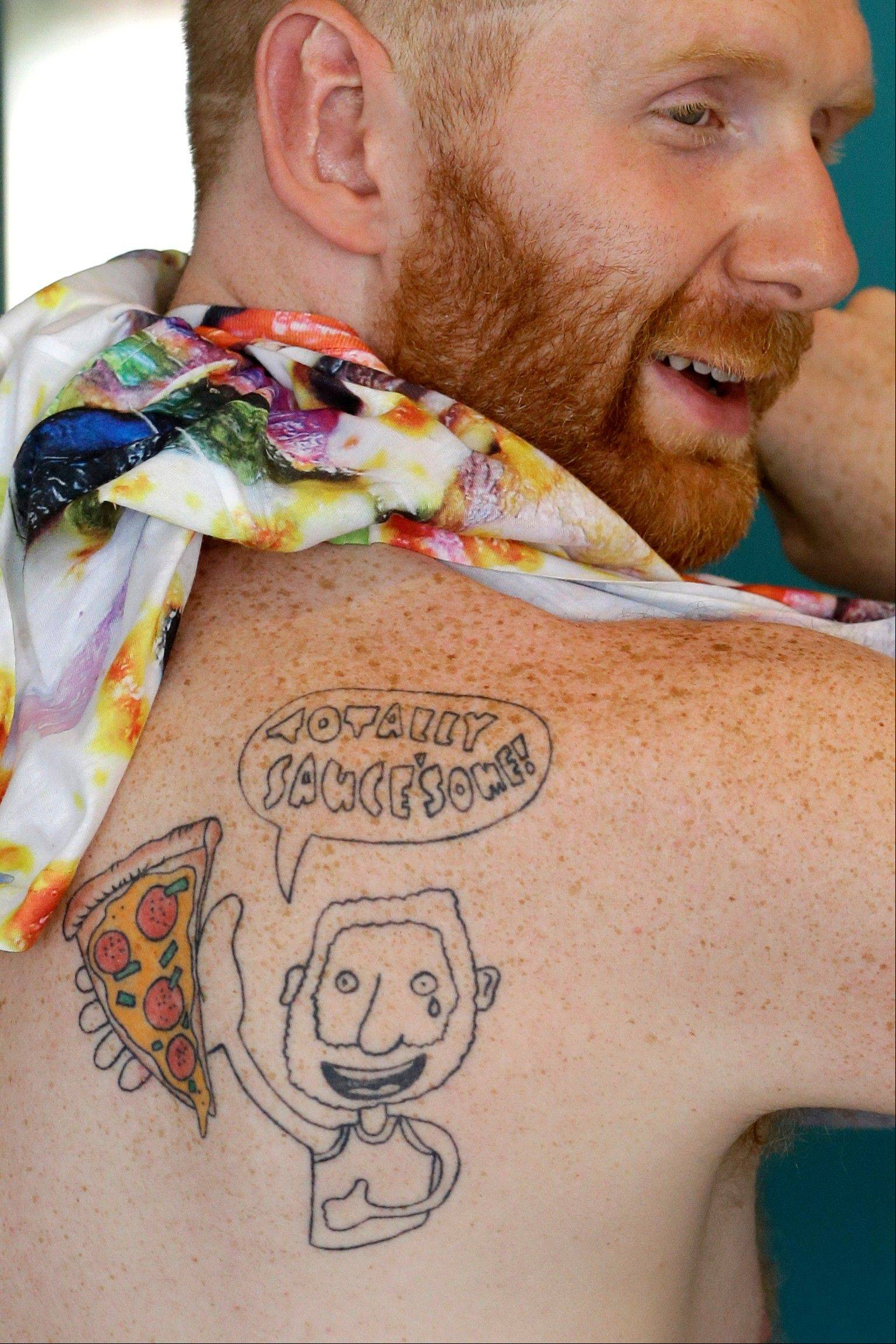 Brian Dwyer displays his tattoo during an interview at Pizza Brain in Philadelphia.