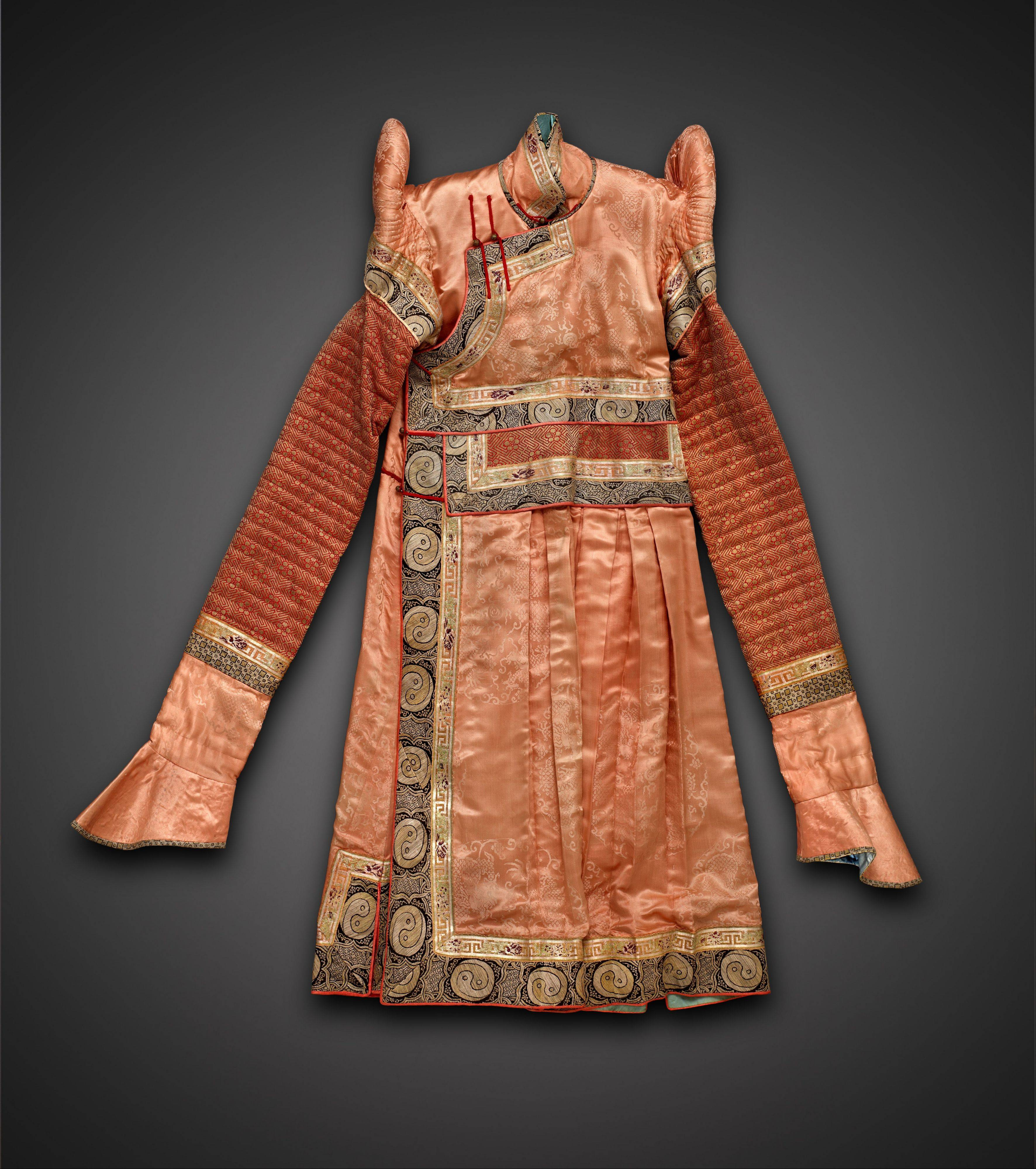 "A brocaded Mongolian silk tunic is called a ""deel."" It was most likely worn during ceremonial occasions."