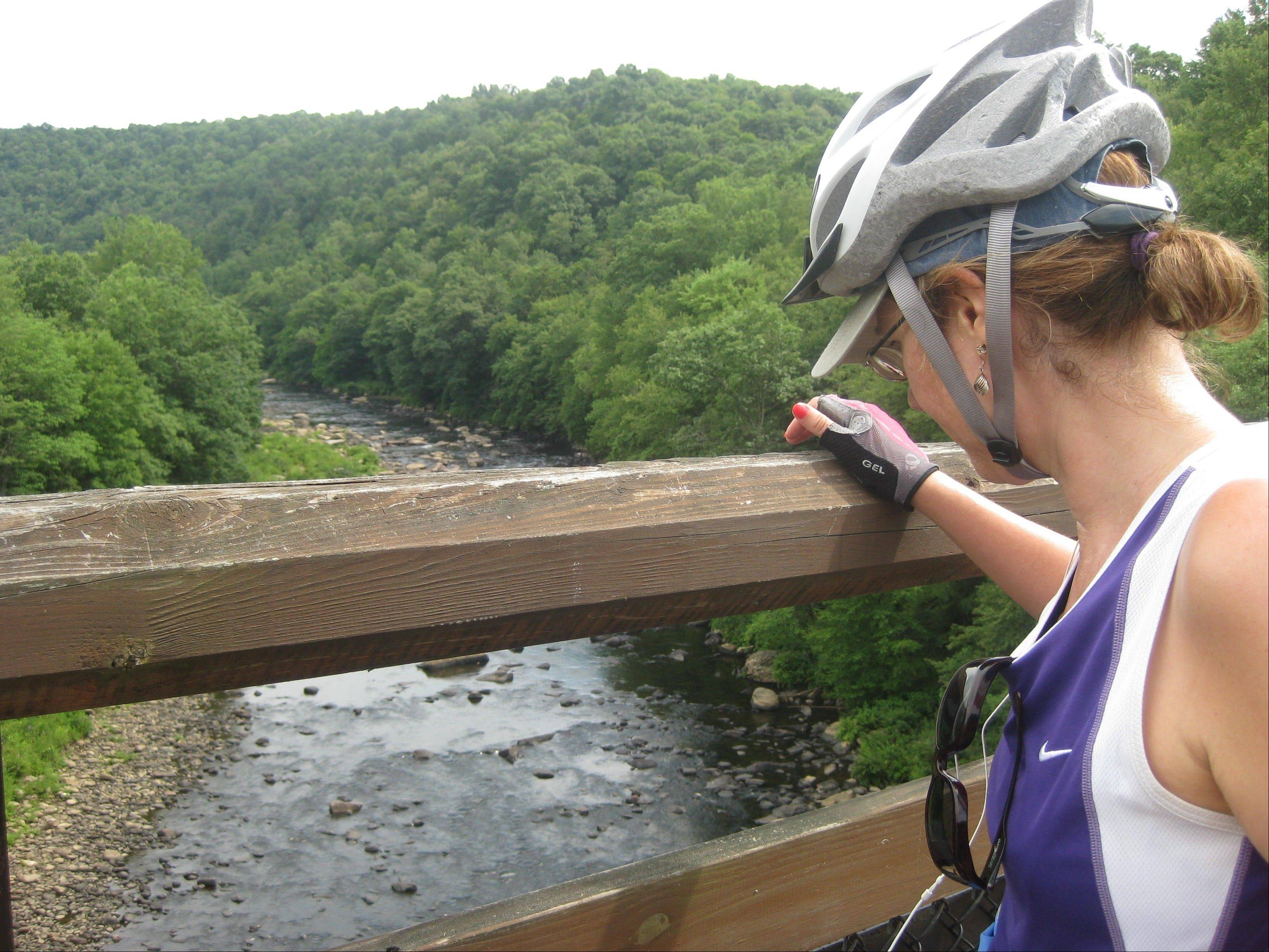 A bicyclist takes in the river view approaching Ohiopyle, Pa., on the Great Allegheny Passage.