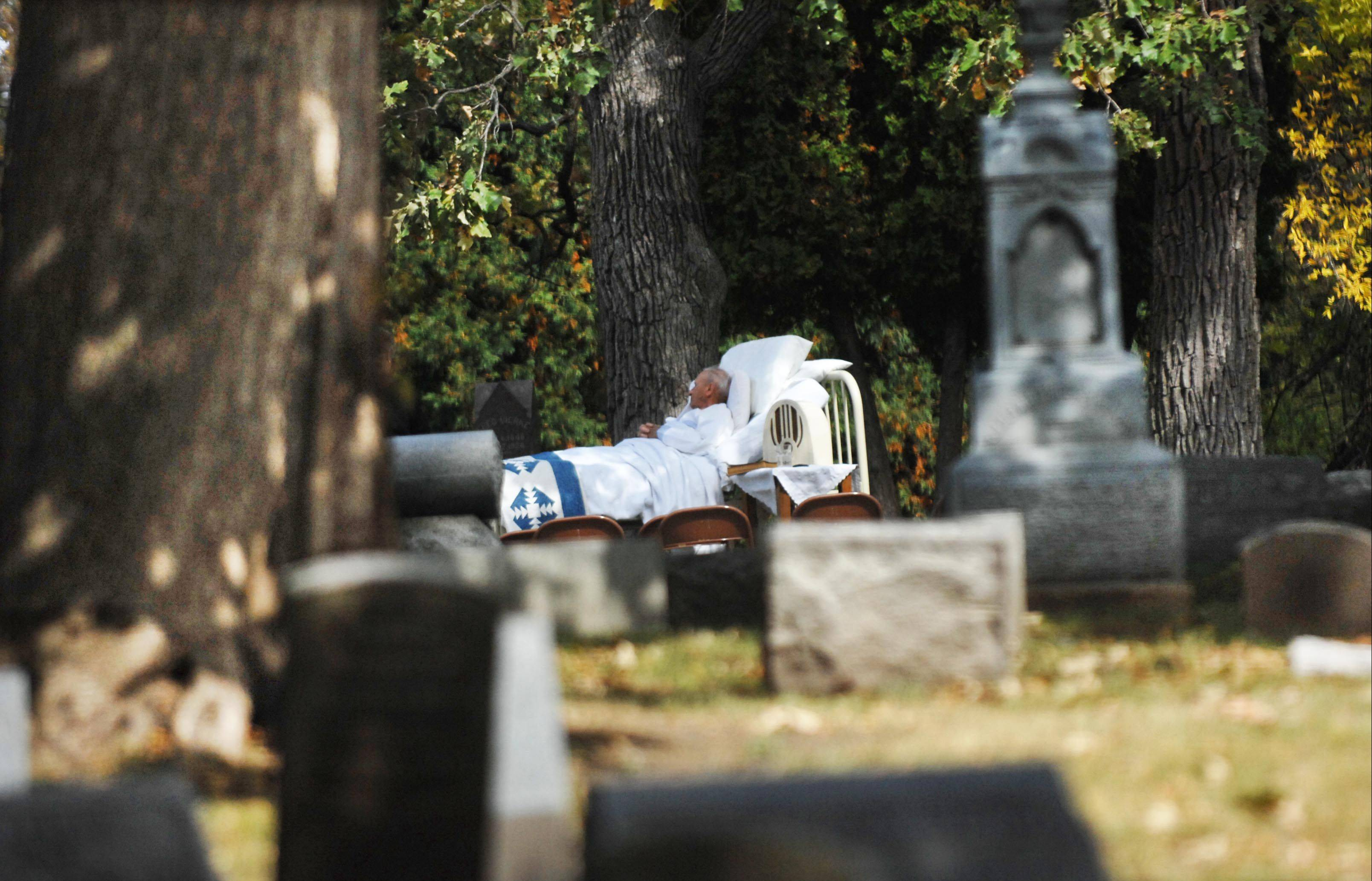 "Jim Anderson lays in an antique bed on a hill in Bluff City Cemetery Sunday during the 25th Annual Cemetery Walk. He was portraying Francis ""Shanty"" Pask, who was a carpenter paralyzed in a fall, and whose mother, Mary Ann, donated a house to Sherman Hospital with the stipulation that her son would be cared for until his death. He died in 1940. She died in 1919 and was portrayed by Sara Ellen Pask. The Elgin Historical Society sponsors the event every year."