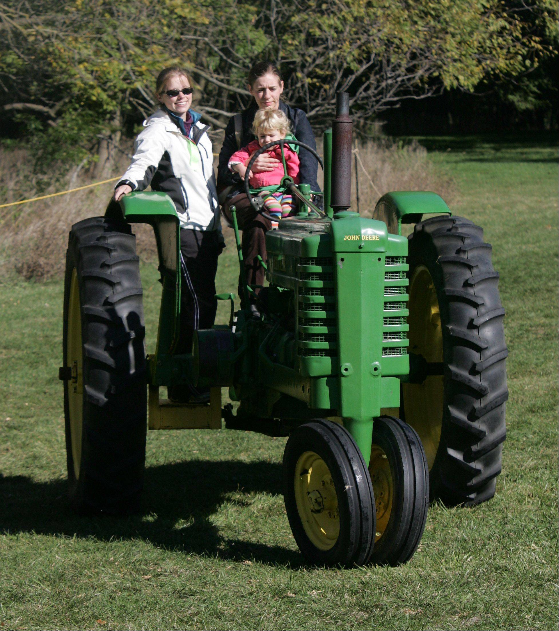 Dana Allan, of Libertyville, with her daughter, Indy, 2, in her lap, drive a 1941 B John Deere tractor with Rebecca Swanson during the 20th Annual Farm Heritage Festival Sunday at Lakewood Forest Preserve near Wauconda. The event was co-sponsored by the Lake County Discovery Museum and the Lake County Farm Heritage Association.
