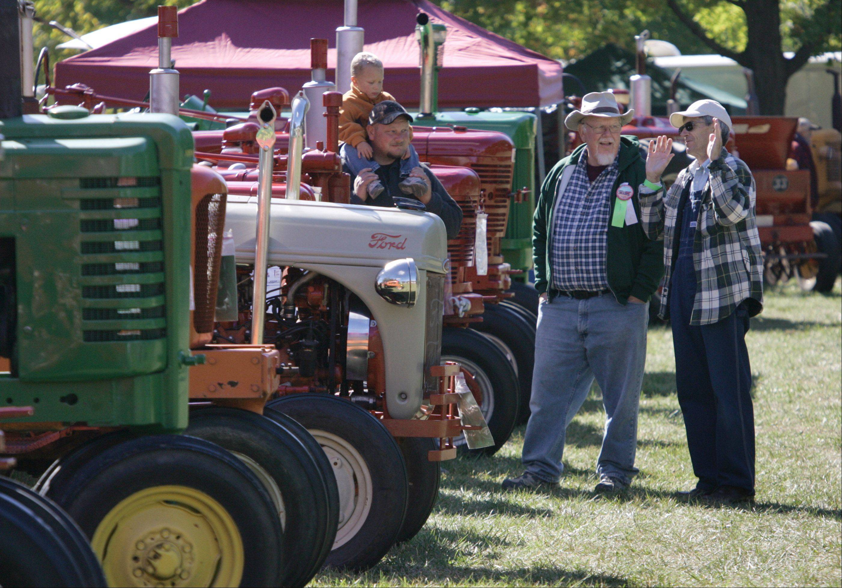 Ron Vaughan, of Wauconda, right, talks about tractors with Will Werhane, of Grayslake, during the 20th Annual Farm Heritage Festival Sunday at Lakewood Forest Preserve near Wauconda. The event was co-sponsored by the Lake County Discovery Museum and the Lake County Farm Heritage Association.