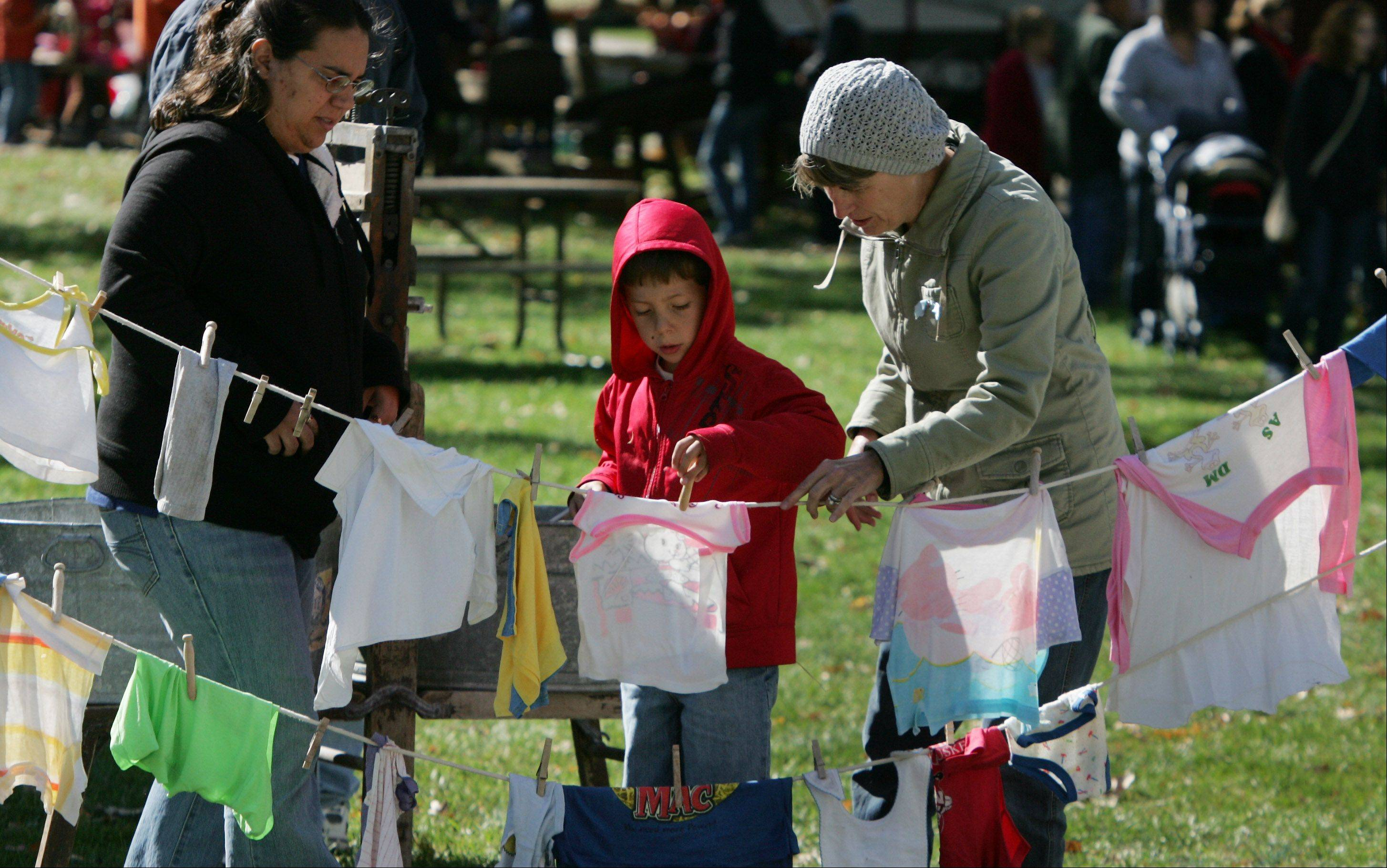 James Hamilton, 6, of Wauconda, hangs clothes on a line with help from his grandmother, Diane, right, and his mother, Carla, after washing them on an old washboard during the 20th Annual Farm Heritage Festival Sunday at Lakewood Forest Preserve near Wauconda. The event was co-sponsored by the Lake County Discovery Museum and the Lake County Farm Heritage Association.