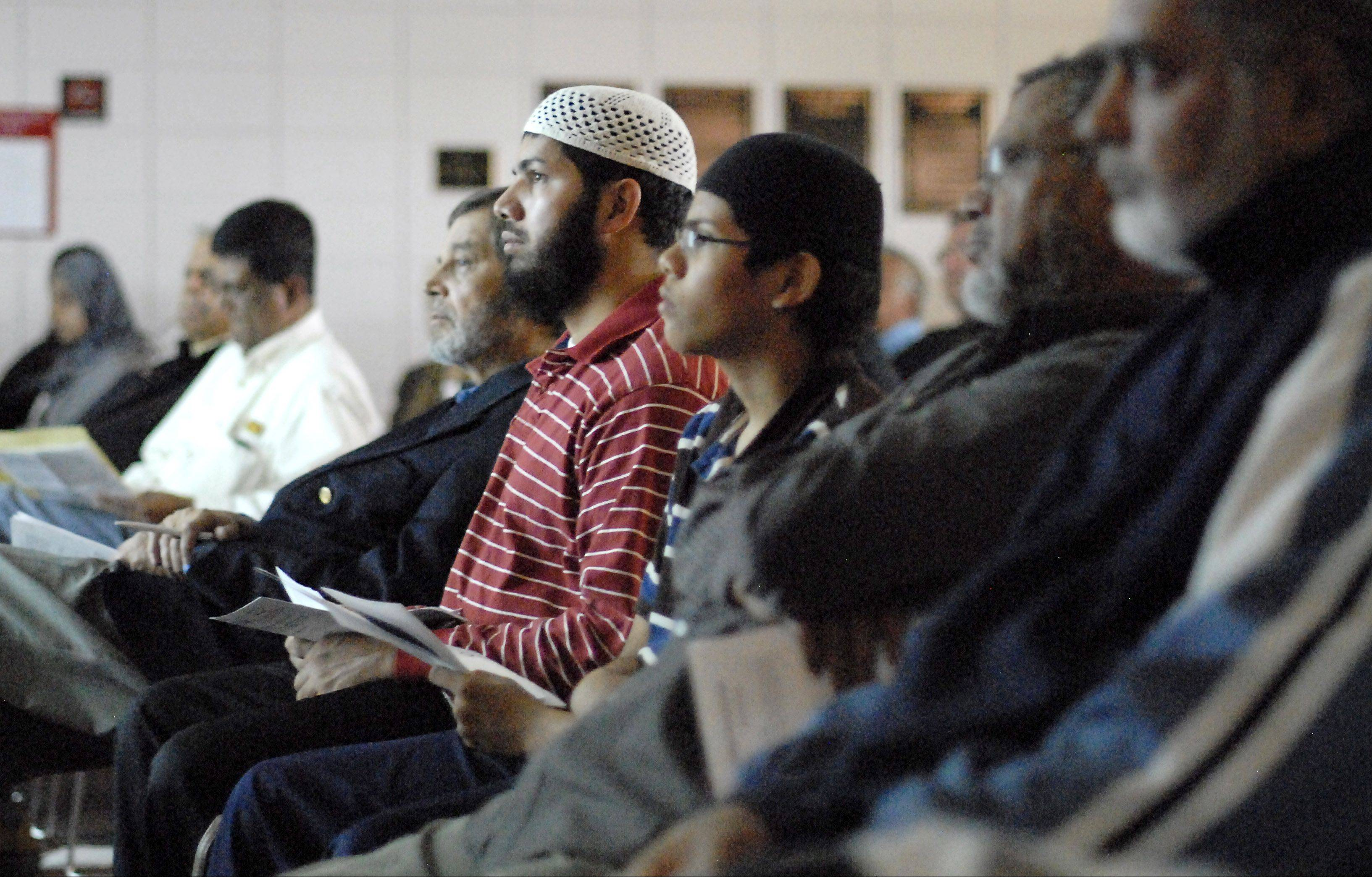 "Attendees look at facts and images while Gerald Hankerson, outreach coordinator for CAIR-Chicago, speaks Saturday at Hanover Park's forum called, ""Who are my Muslim neighbors?"" The event was sponsored by the village's Cultural Inclusion & Diversity Committee."