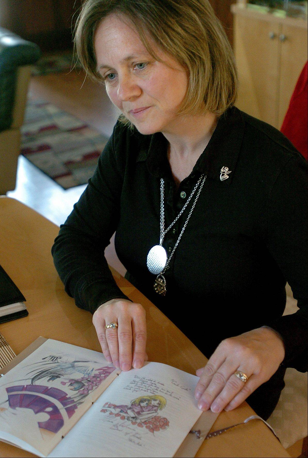 Margaret Skrzypkowski looks through a book made up of her daughter Monika's drawings.