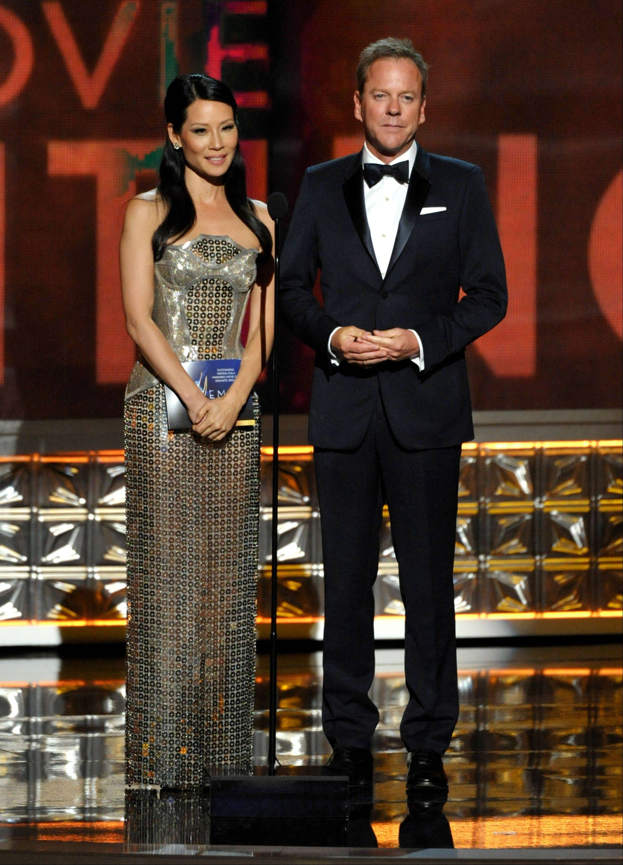 """Elementary"" star Lucy Liu, left, and Kiefer Sutherland present an award onstage."