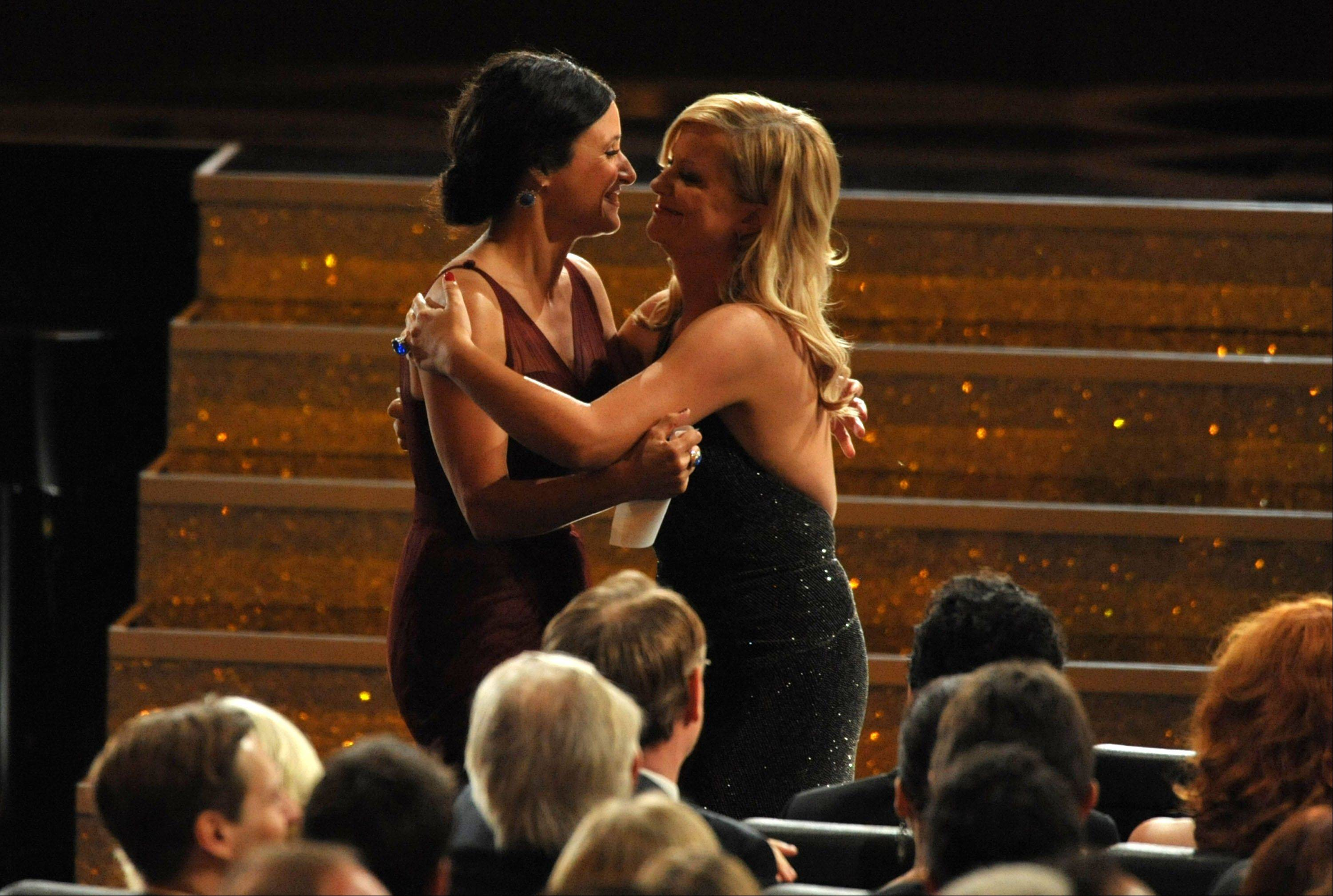 "Amy Poehler, right, congratulates Julia Louis-Dreyfus as she walk onstage to accept the award for outstanding lead actress in a comedy series for ""Veep."""