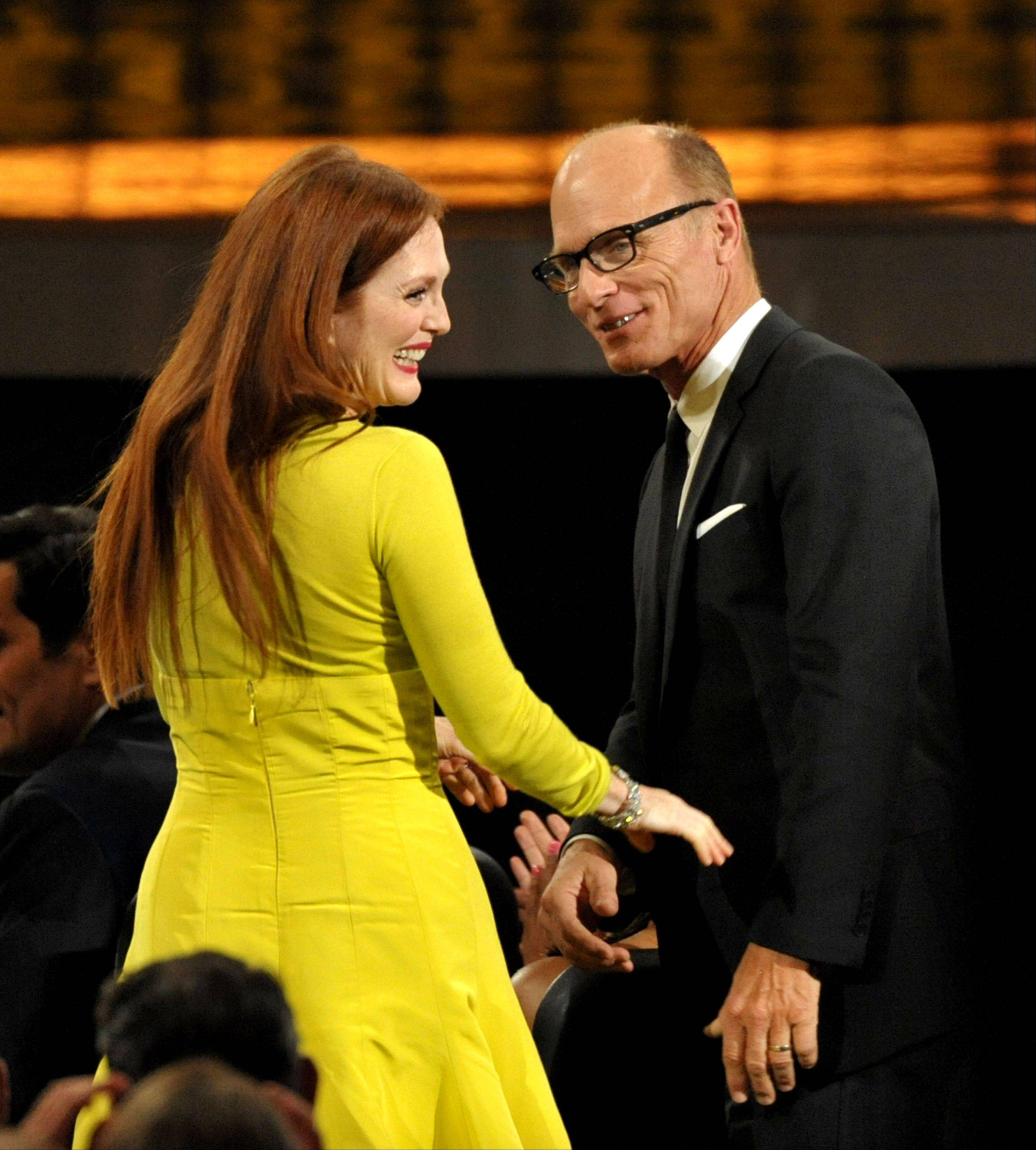 "Ed Harris, right, congratulates Julianne Moore as we walks onstage to accept the award for outstanding lead actress in a miniseries or movie for ""Game Change."""