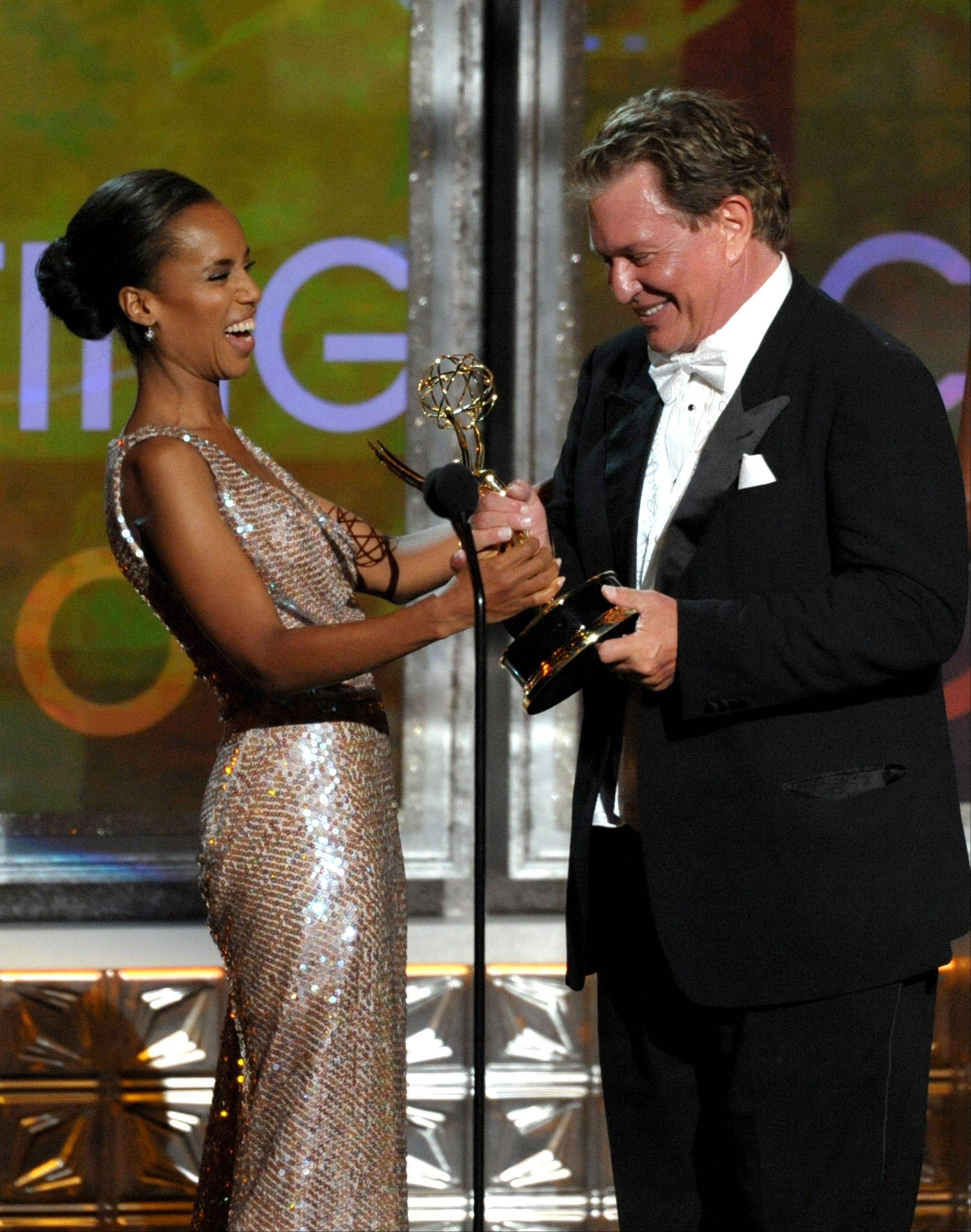 """Scandal"" star Kerry Washington, left, presents the award for Outstanding Supporting Actor In A Miniseries Or Movie to Tom Berenger for ""Hatfields & McCoys."""