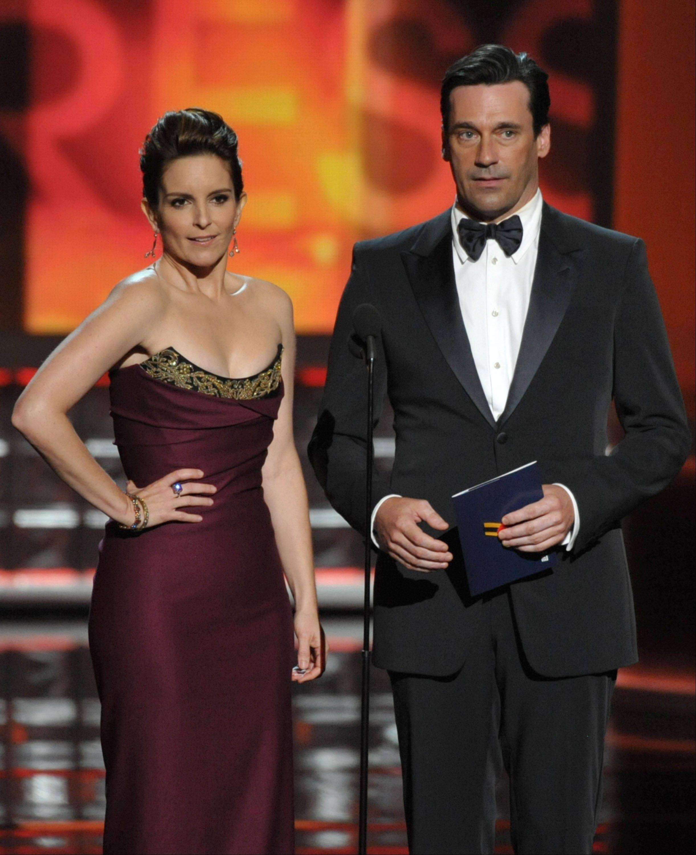 Tina Fey, left, and Jon Hamm present an award onstage at the 64th Primetime Emmy Awards.
