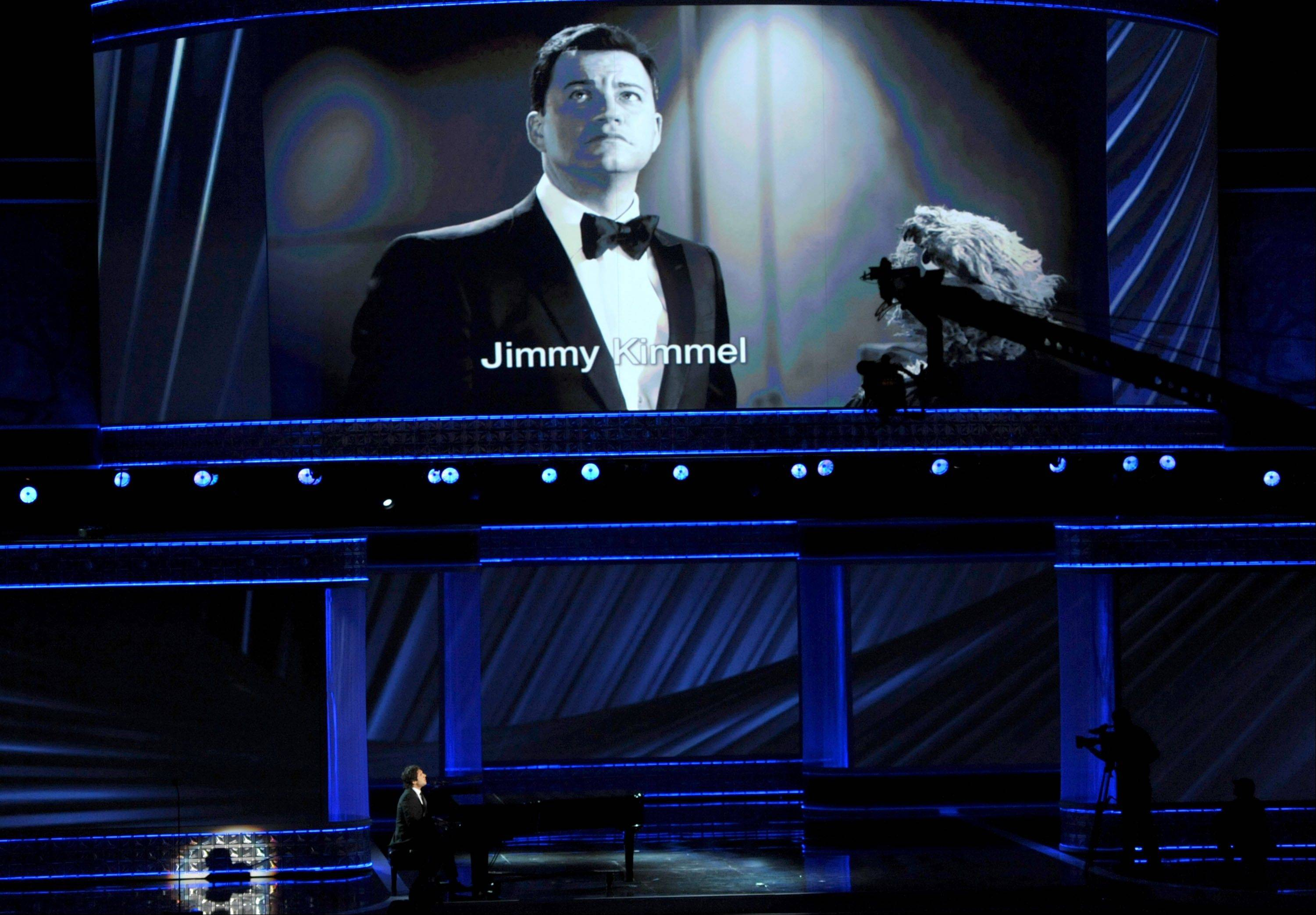 Josh Groban, left, and Jimmy Kimmel, onscreen, perform at the 64th Primetime Emmy Awards.