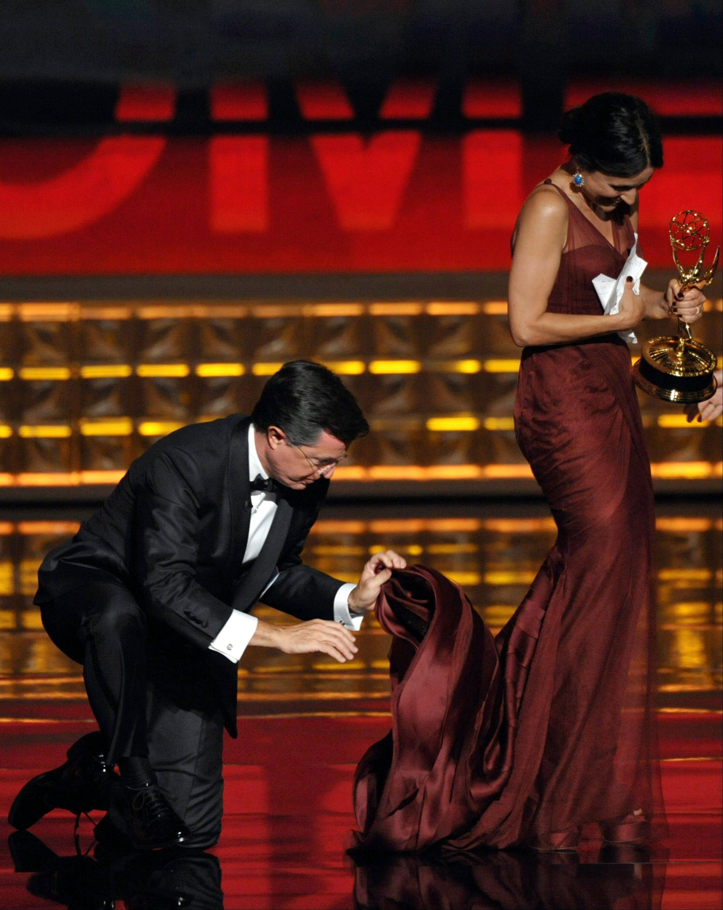 "Stephen Colbert, left, holds on to the dress of Julia Louis-Dreyfus as she accepts the award for Outstanding Lead Actress in a Comedy Series for ""Veep."""