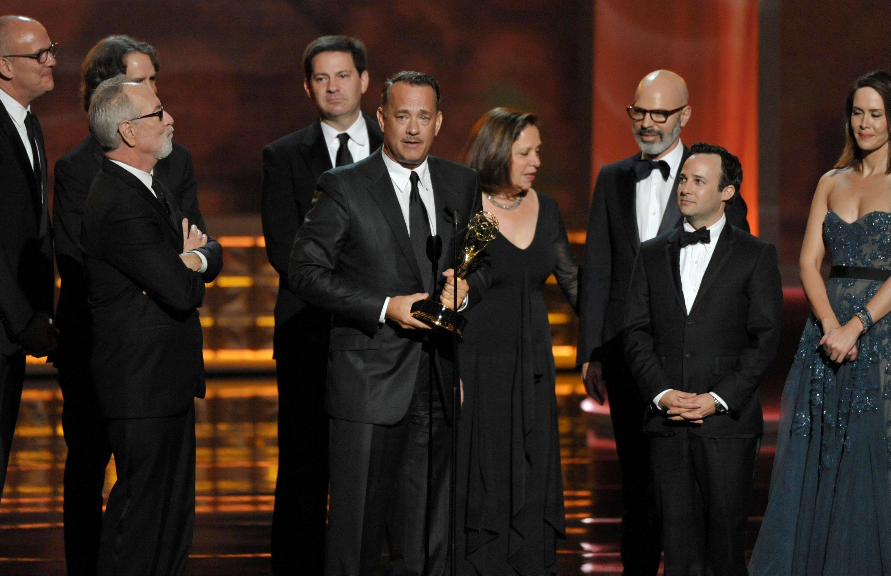 "Tom Hanks, center, and the cast and crew of ""Game Change"" accept the award for outstanding miniseries or movie."