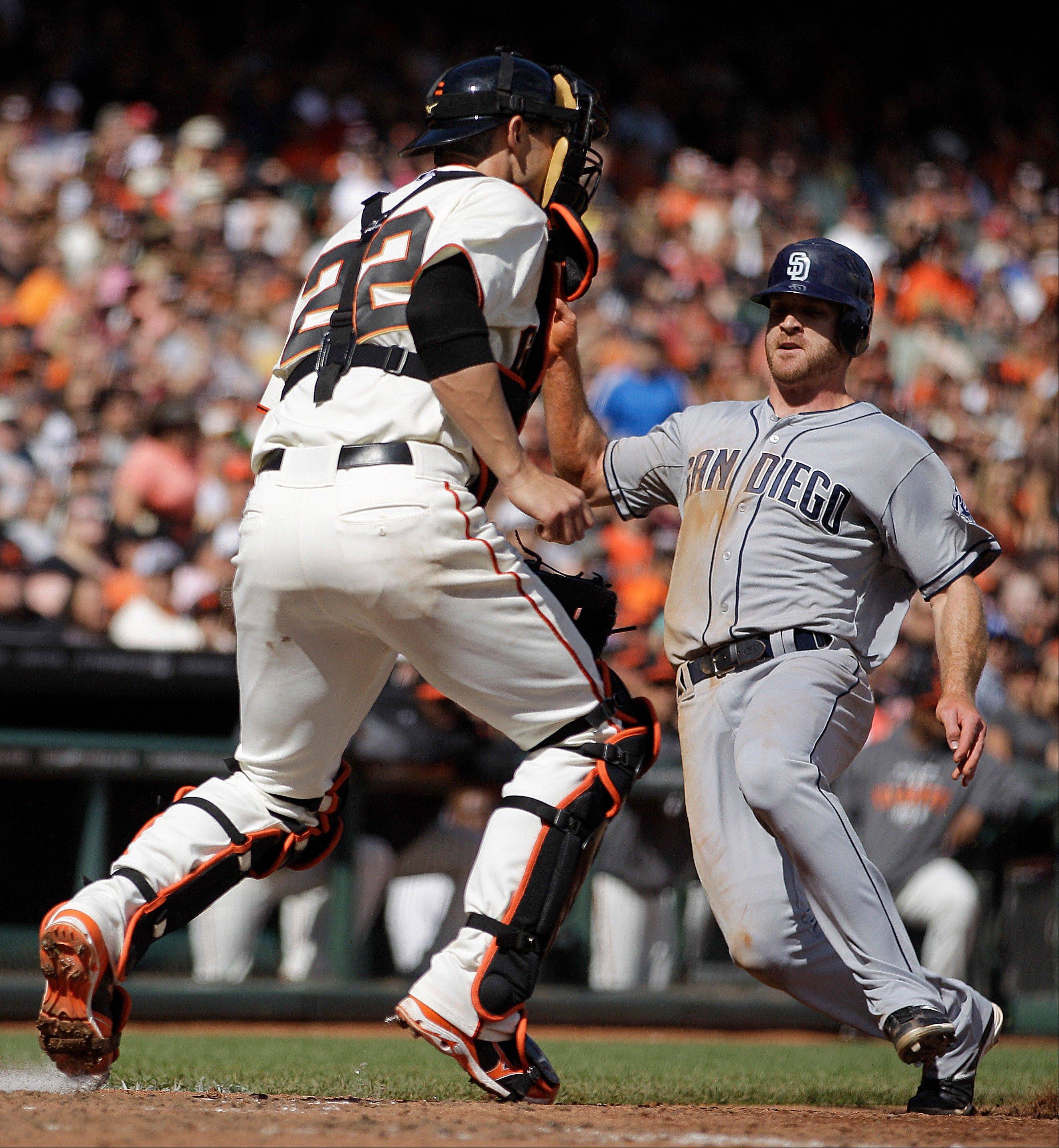 The Padres' Logan Forsythe slides past San Francisco Giants catcher Eli Whiteside in the fifth inning Sunday in San Francisco. Forsythe scored on a single by Yasmani Grandal.