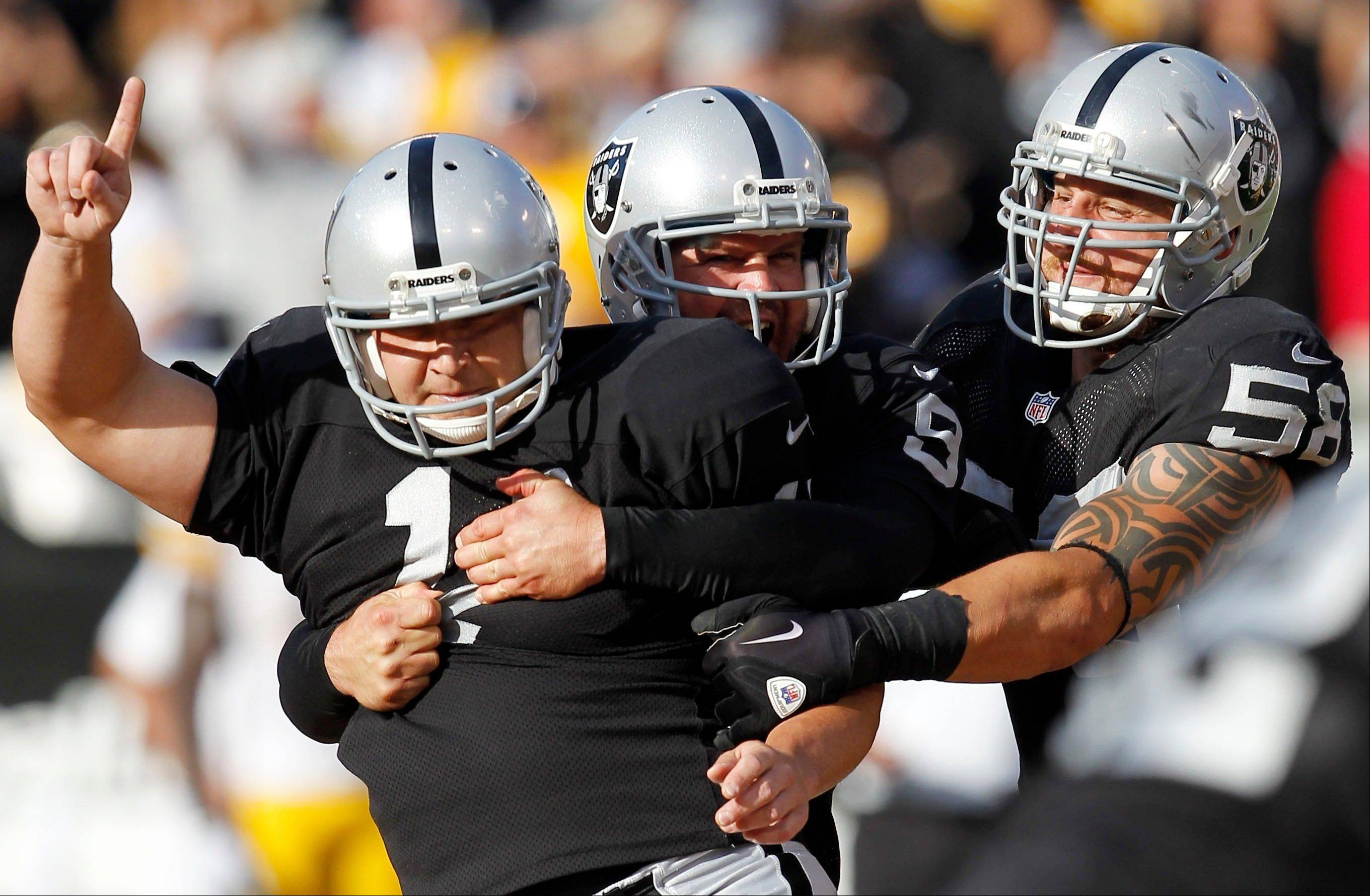 Raiders kicker Sebastian Janikowski (11) celebrates with holder Shane Lechler (9) and Dave Tollefson (58) after Janikowski's 43-yard field goal to win the game against the Pittsburgh Steelers on Sunday in Oakland, Calif.