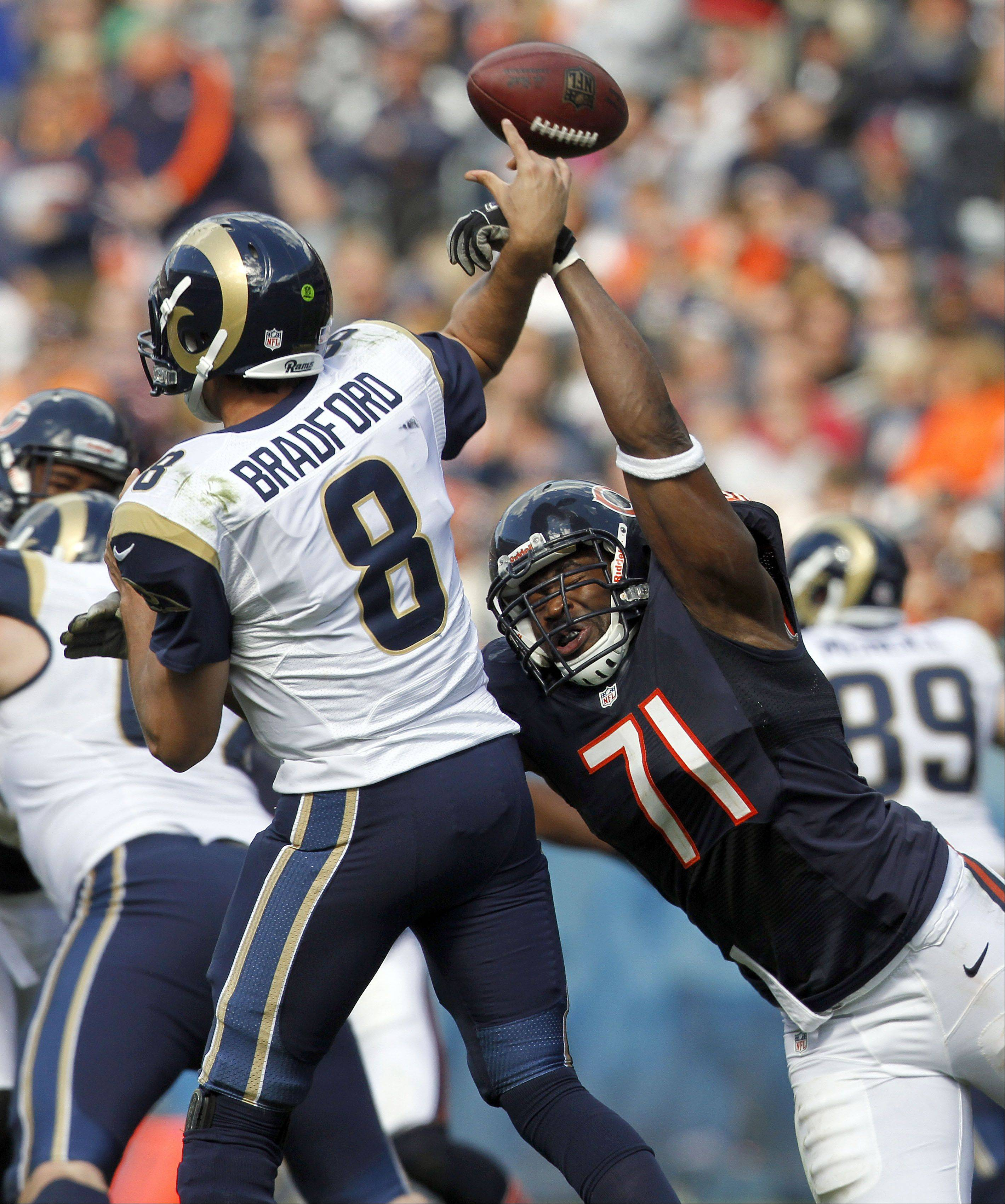 Bears defensive end Israel Idonije hits St. Louis Rams quarterback Sam Bradford's arm as he throws during the Bears 23-6 win Sunday at Soldier Field in Chicago.