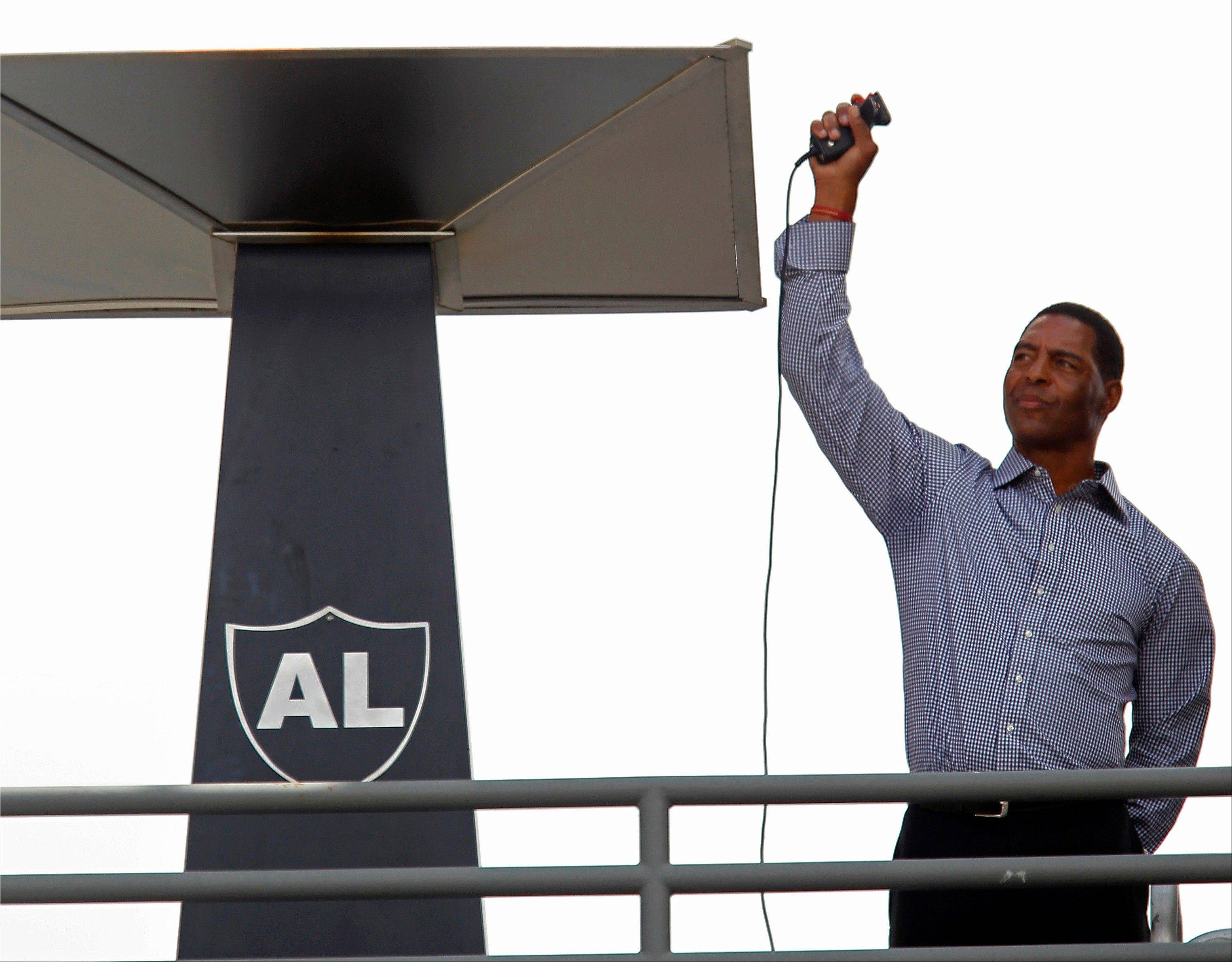Former Raiders great Marcus Allen lights the eternal flame for the late owner Al Davis before Sunday's game against the Pittsburgh Steelers in Oakland, Calif.