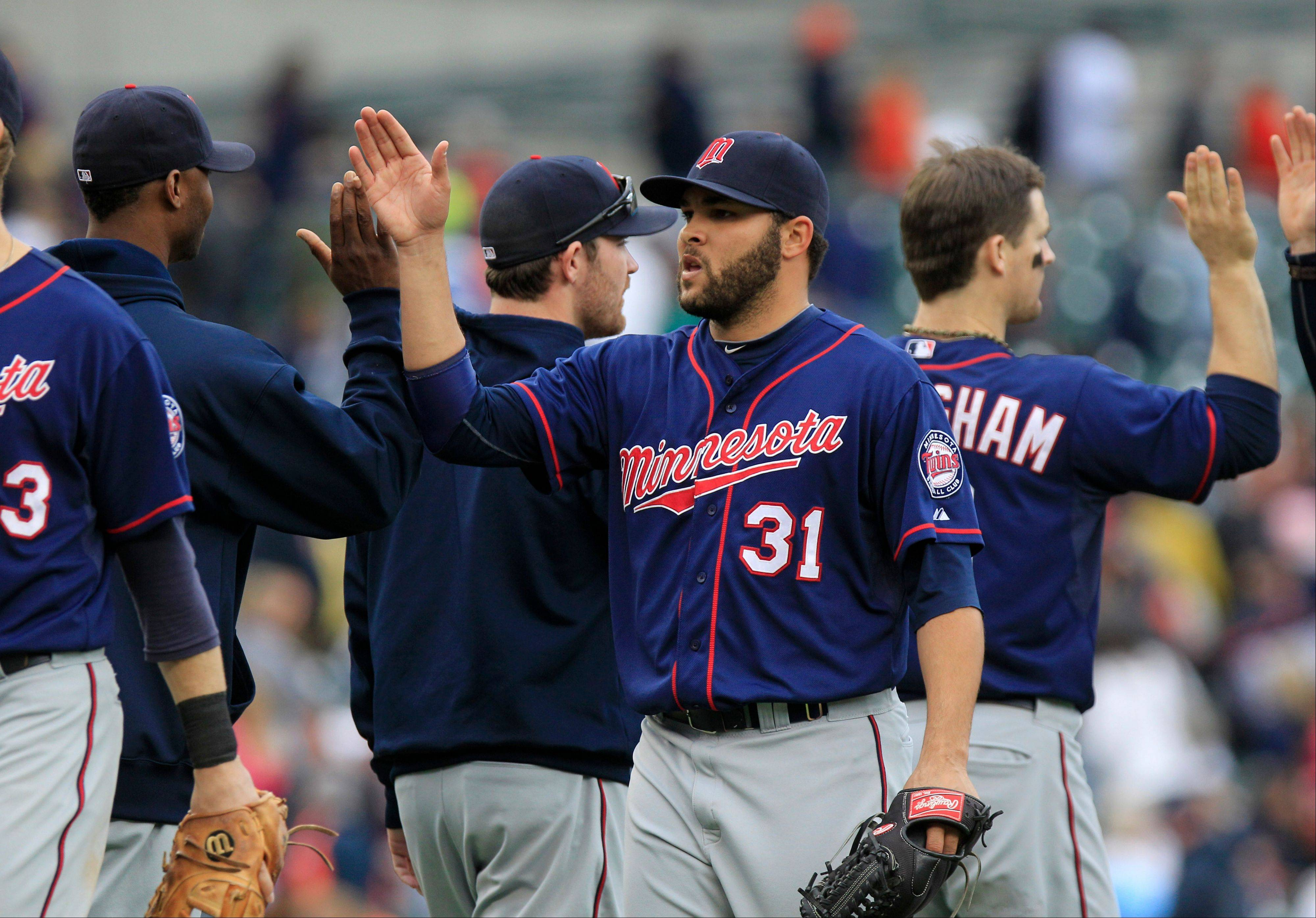 Twins relief pitcher Alex Burnett (31) high-fives his teammates after their 10-4 win over the Detroit Tigers in the first game of a doubleheader Sunday at Comerica Park.
