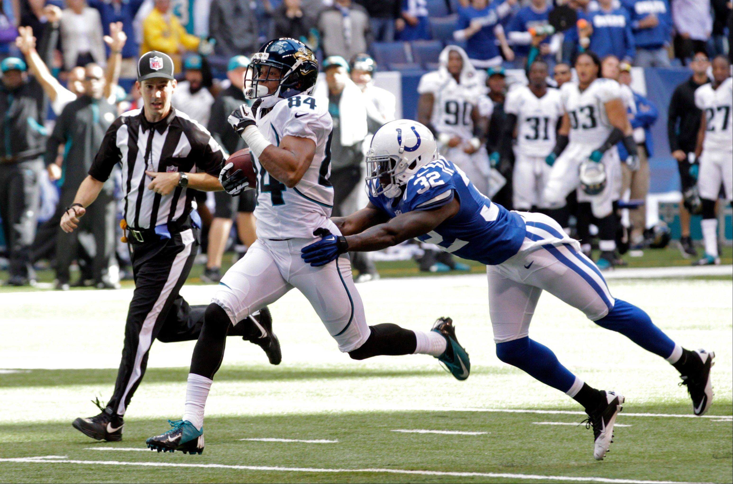 Jacksonville Jaguars wide receiver Cecil Shorts breaks the tackle of Indianapolis Colts defensive back Cassius Vaughn on his way to 80-yard touchdown in the final minute of Sunday's game in Indianapolis.