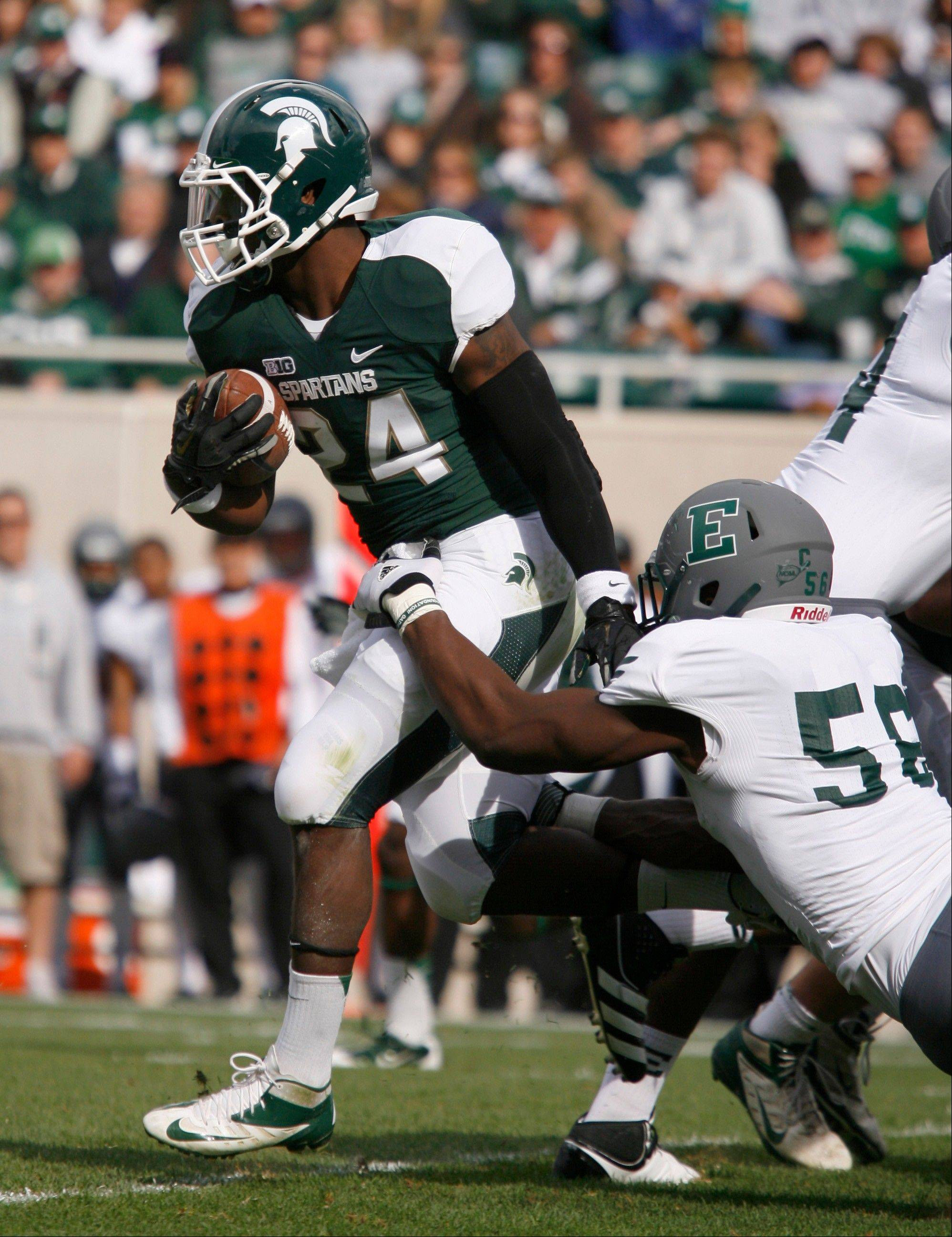 Michigan State's Le'Veon Bell, left, escapes the grasp of Eastern Michigan's Andy Mulumba during the first quarter Saturday in East Lansing, Mich.