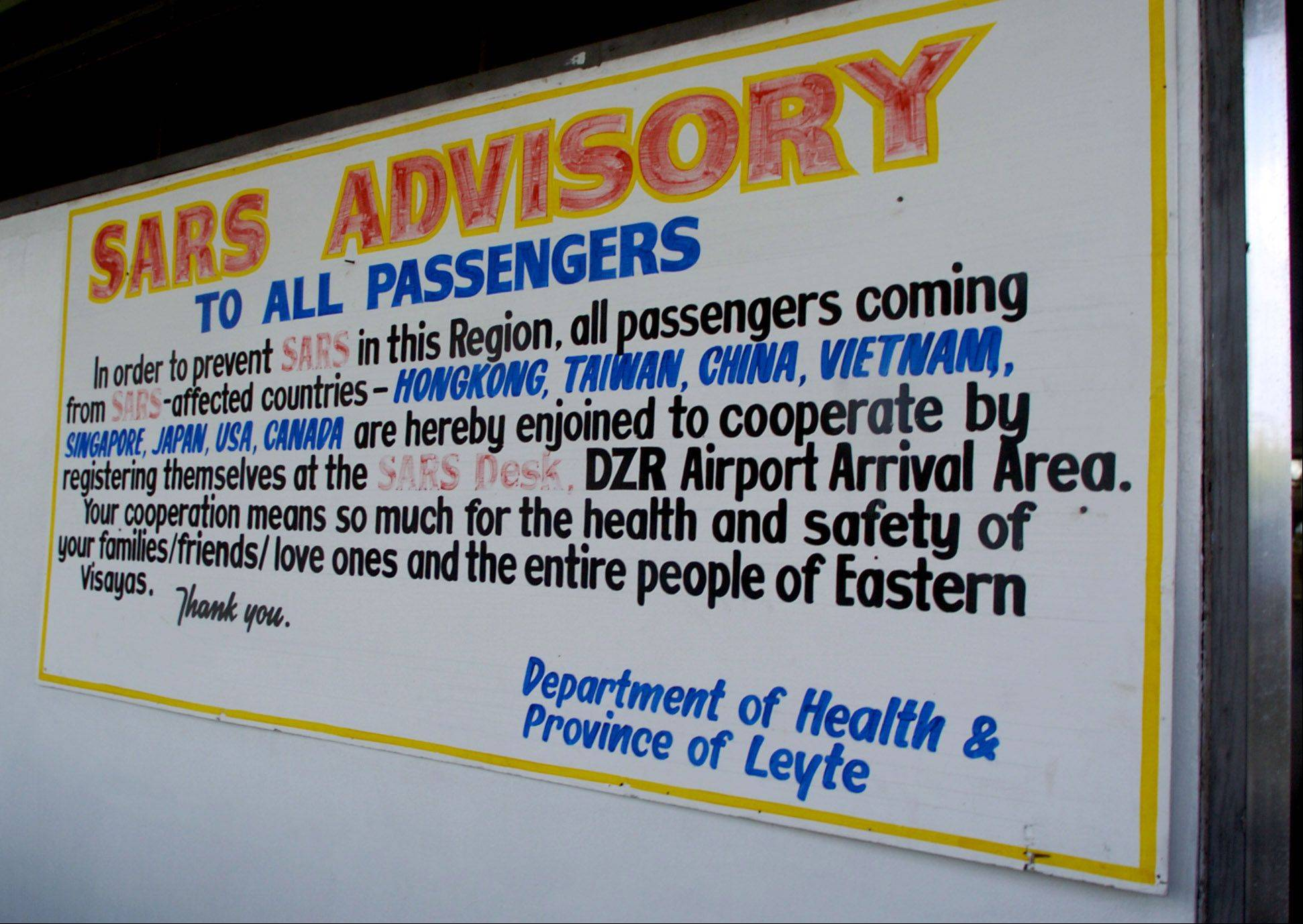 DAILY HERALD/MARK WELSH A SARS warning is seen at the entrance of the Leyte-Tacloban airport in the Philippines during the SARS outbreak in 2003.