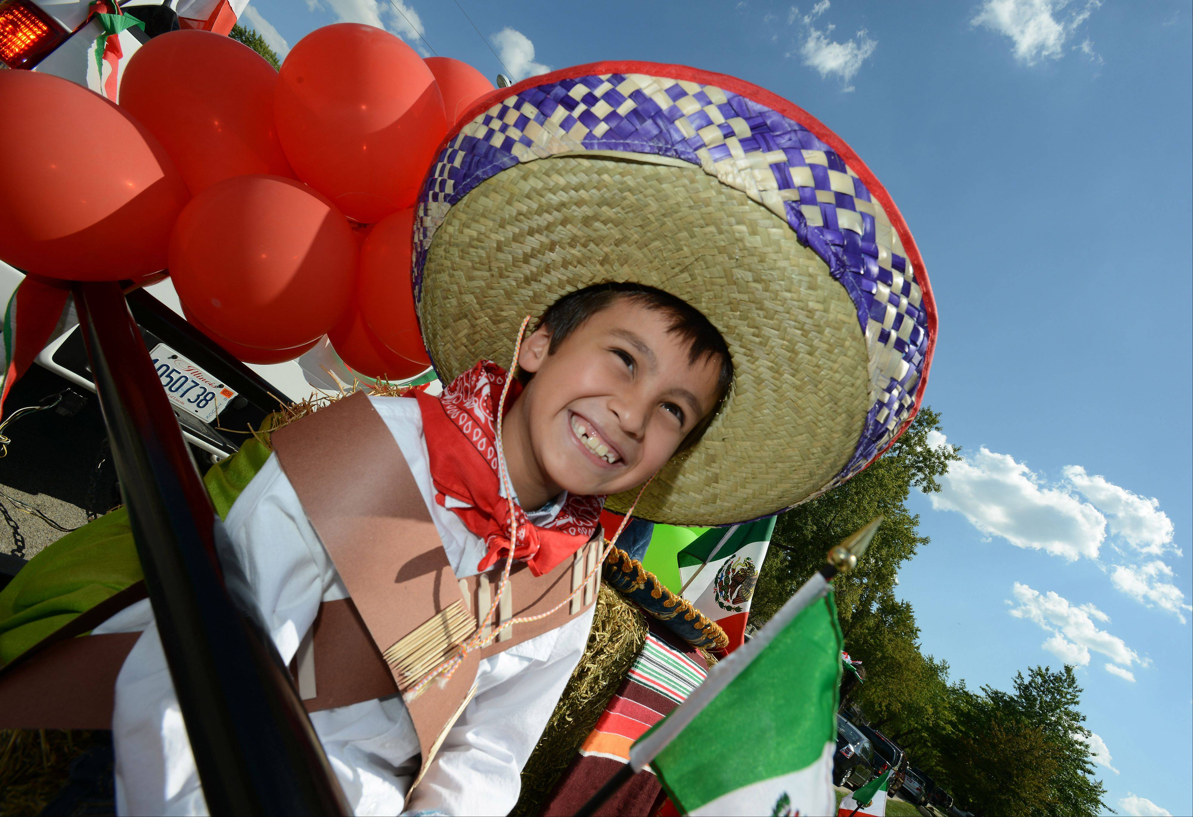 Oscar Medina, 7, of Hanover Park is all smiles as he rides in the Mexican Independence Day parade in Hanover Park on Saturday.