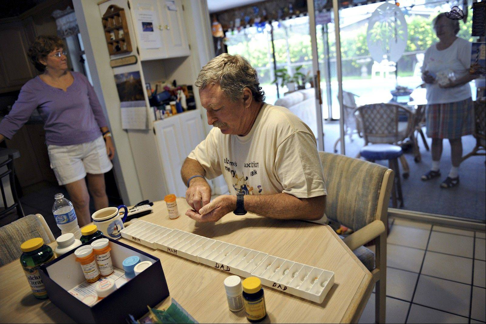 Tom Sinotte organizes his parents' prescription pills as well as their vitamins on the dining room table in their home. Tom's wife, Linda, and his mom, Ardis Sinotte, wait for him to be finished.