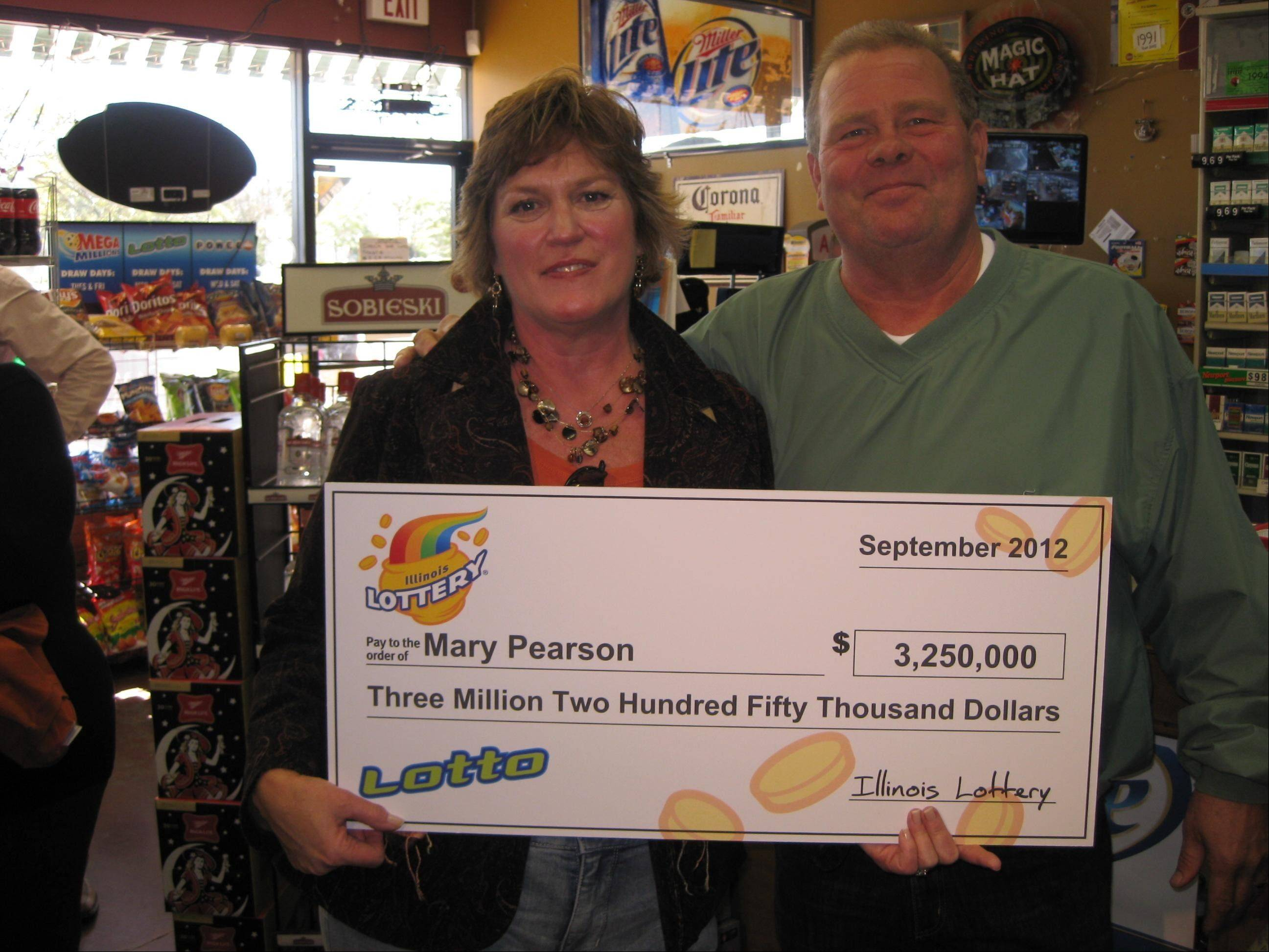 Mary Pearson of Cary holds the winning Quick Pick Lotto game ticket she bought worth $3.25 million. She and her husband, Steve, collected a check for their winnings Monday.