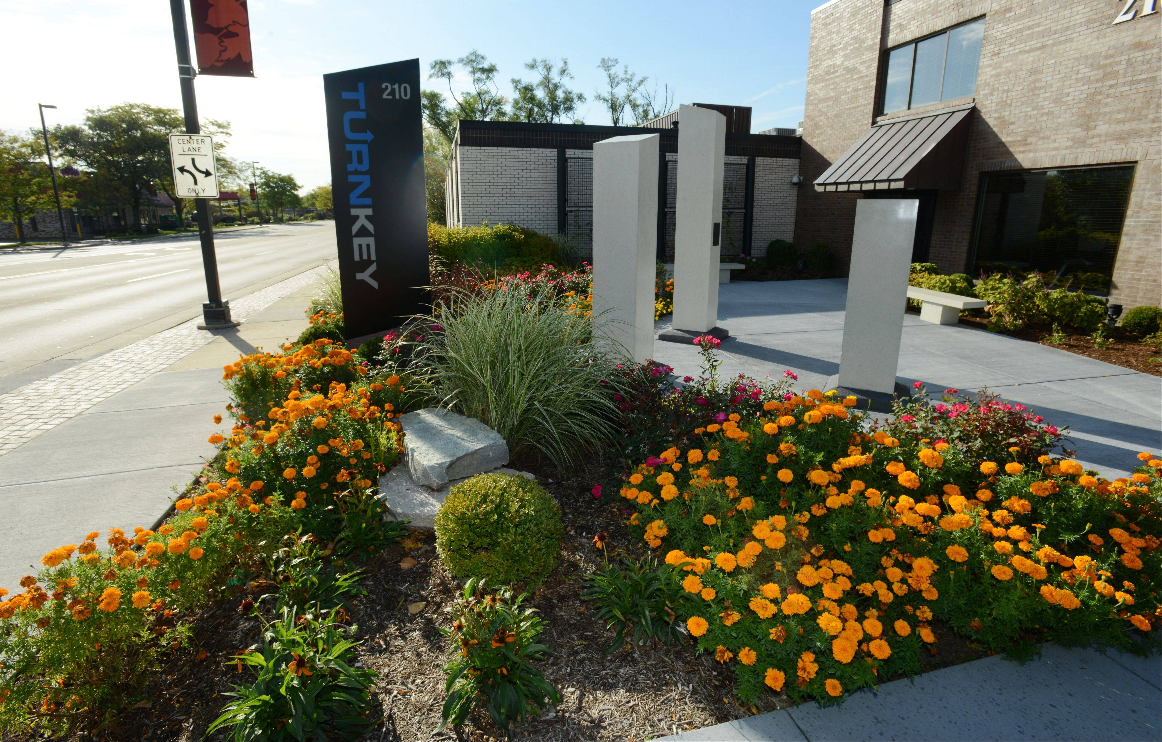 Flowers, tall pillars and concrete benches mark Illumination Park on Milwaukee Avenue in Wheeling.