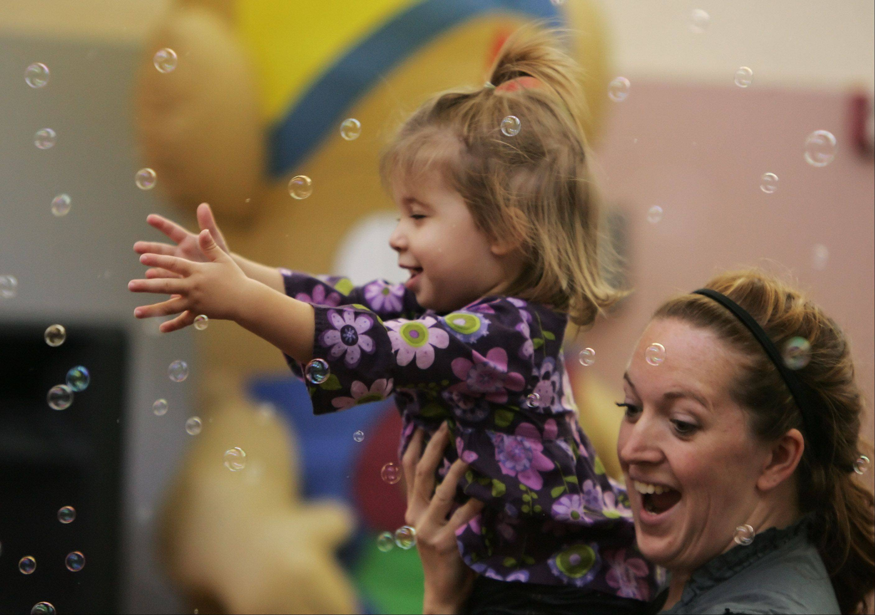 September Larson, of Lindenhurst, holds her niece, Lucy Lewis, as she reaches for bubbles during the Beach Party Tuesday at Lake Villa District Library. Award-winning musician Dave Rudolf entertained children and adults with music and dance as children learn to hula dance and limbo.