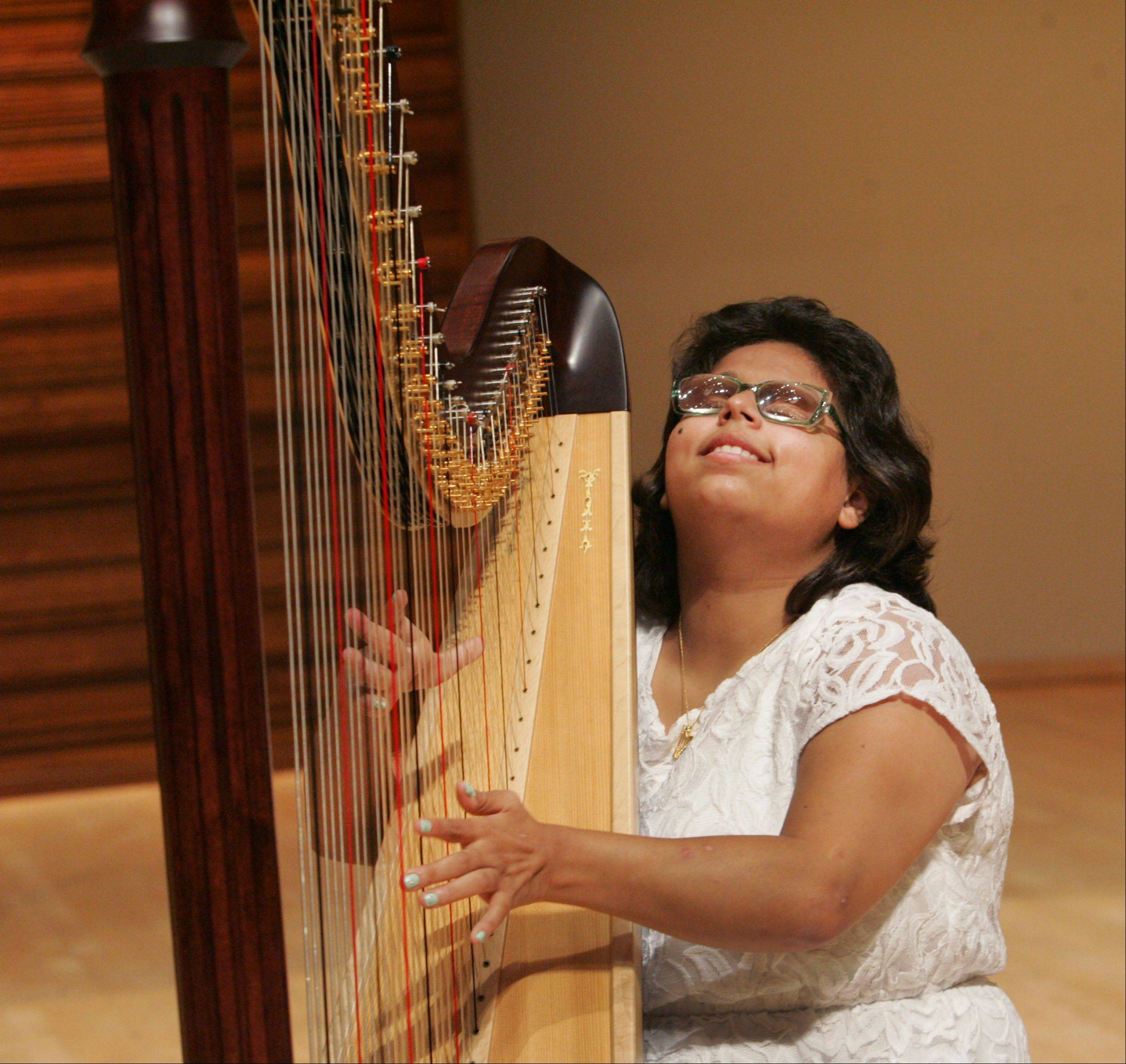 Special Talents America finalist Mia Strayer, 21, of Rockford, plays the harp in Wentz Concert Hall at North Central College in Naperville on Friday. Mia, who is blind and has cerebral palsy, will perform at Wentz Hall with 13 other contestants in the talent competition on November 5.