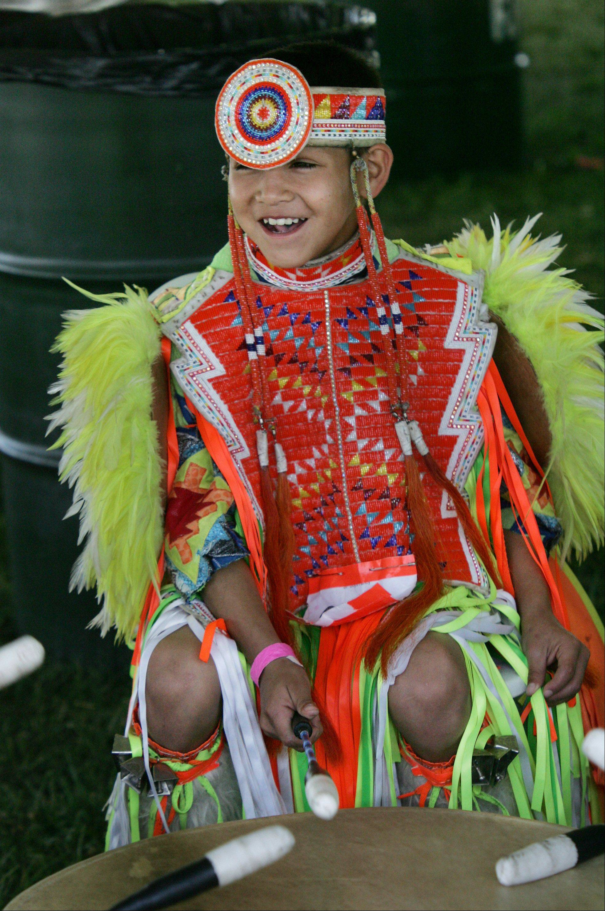 Buster Cleveland, 8, from the Ho Chunk Nation in Wisconsin, plays the drum during the 59th Annual American Indian Center Pow Wow Sunday at Busse Woods Forest Preserve in Elk Grove Village. The event featured Native American dance competition, Native skateboarding demo, singers, artists, food vendors, storytelling, and archery.