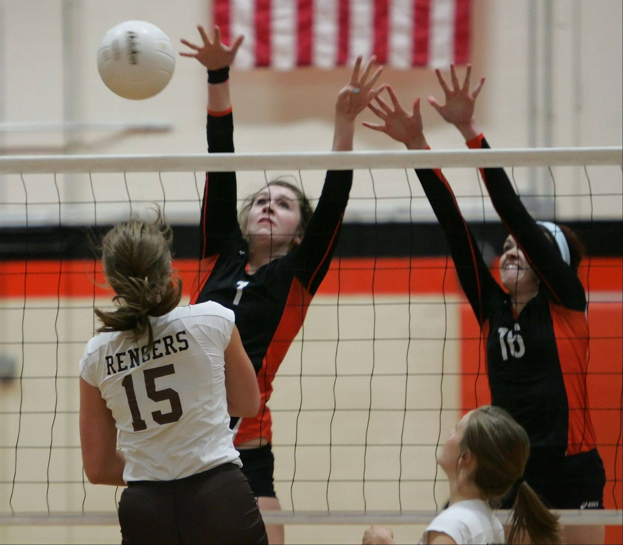 Carmel's Elizabeth Rengers hits the ball past Libertyville blockers Alex Basler and Rhiannon Prentiss on Monday at Libertyville.