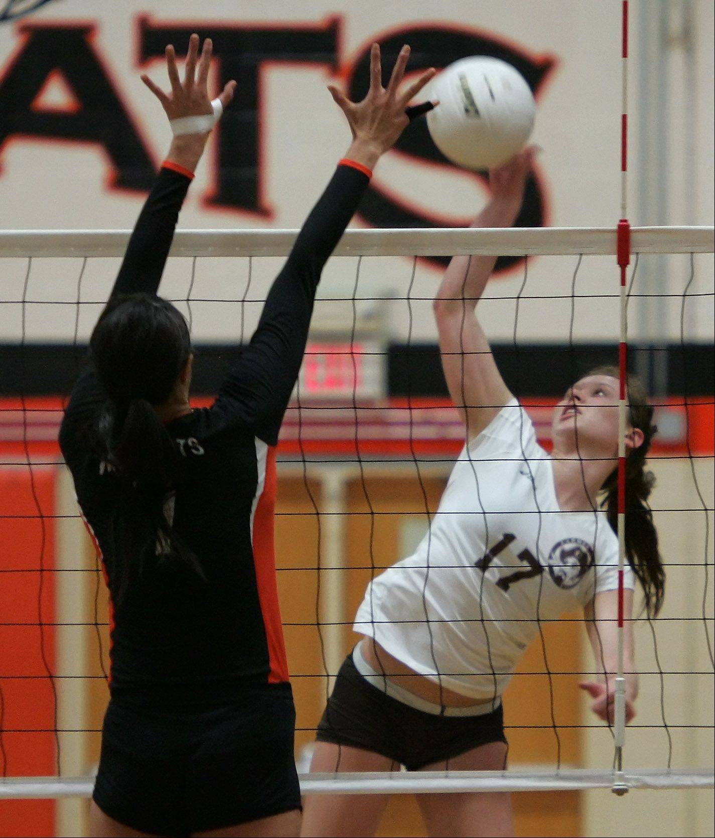 Carmel player Caitlin Barry slams the ball against Libertyville blocker Cindy Zhou on Monday at Libertyville.