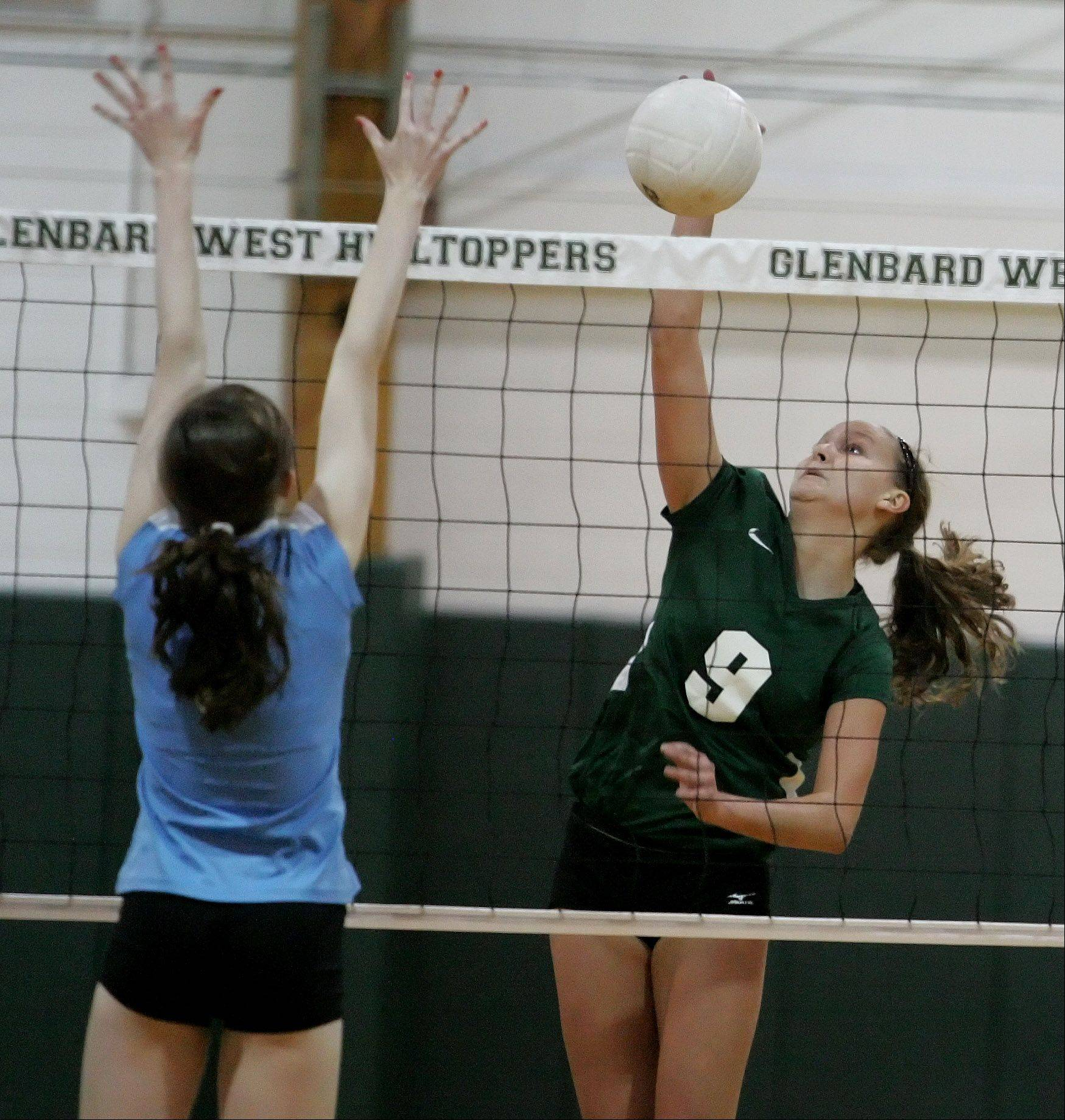 Amanda Perry of Glenbard West spikes the ball in girls volleyball action against Willowbrook on Monday in Glen Ellyn.