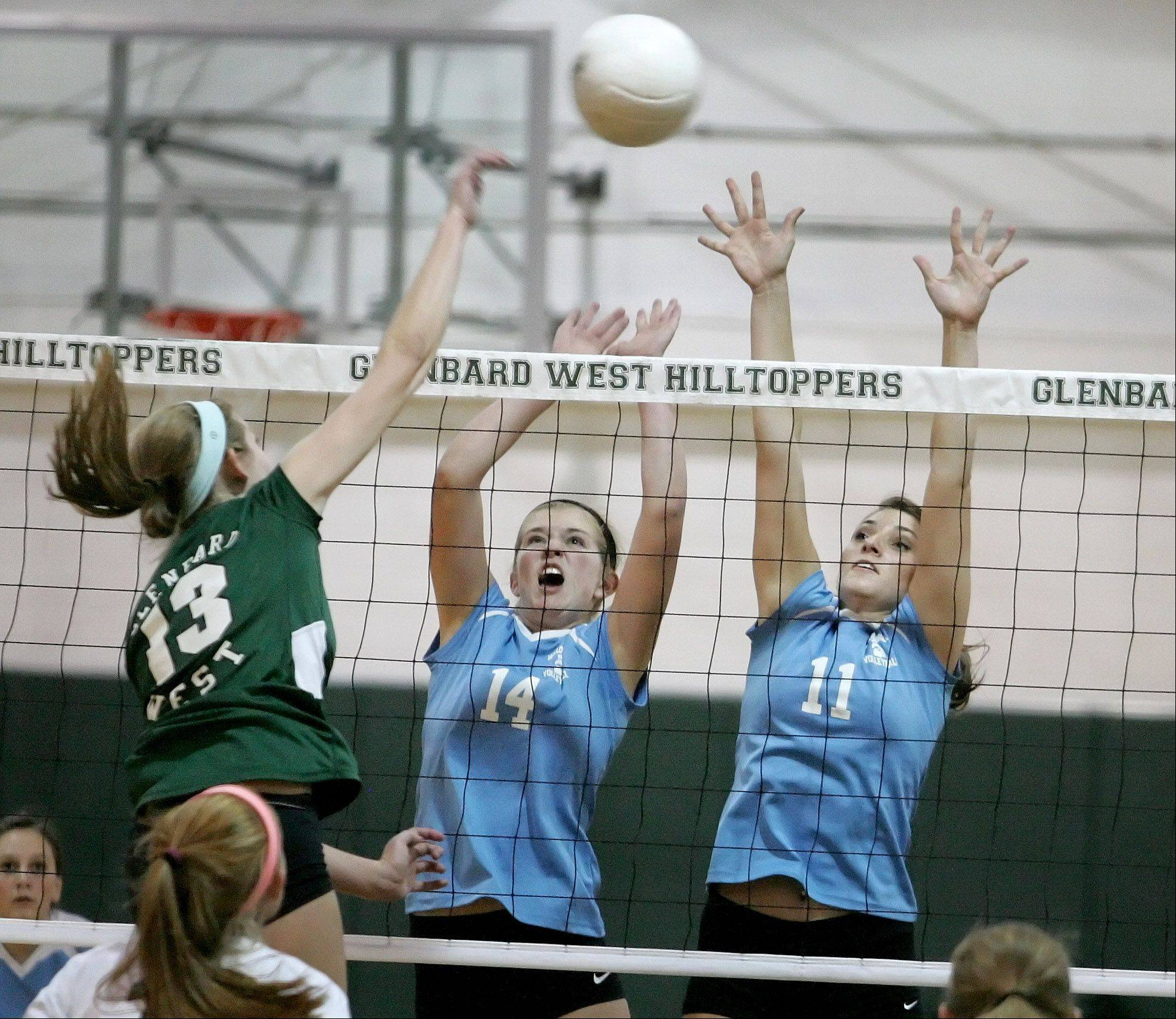 Megan Wagner, left, of Glenbard West htis the ball over Lauren Carroll, center and Michelle Herz, right, of Willowbrook in girls volleyball action on Monday in Glen Ellyn.