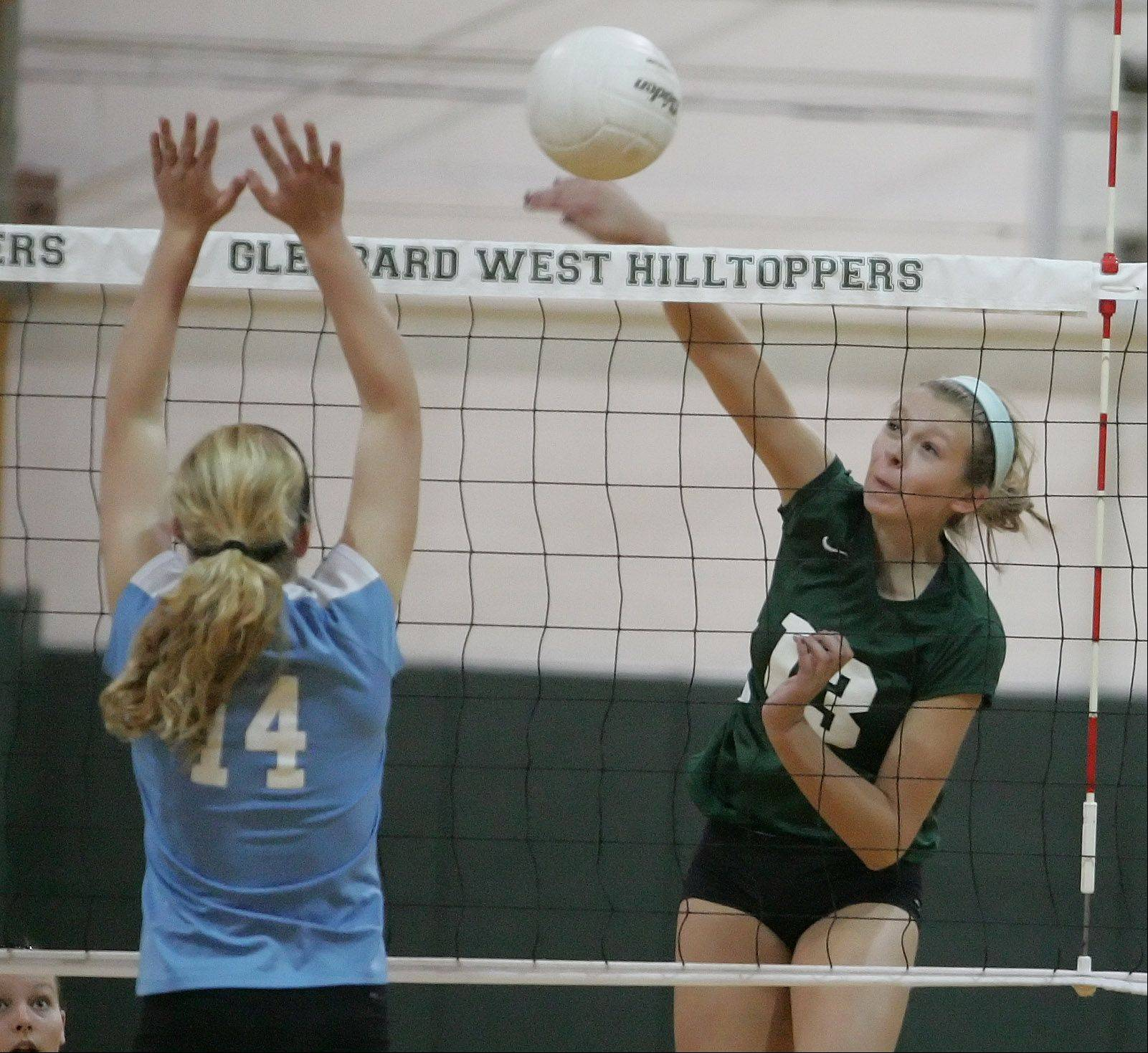 Megan Wagner of Glenbard West spikes the ball as Lauren Carroll of Willowbrook goes up to block in girls volleyball action on Monday in Glen Ellyn.