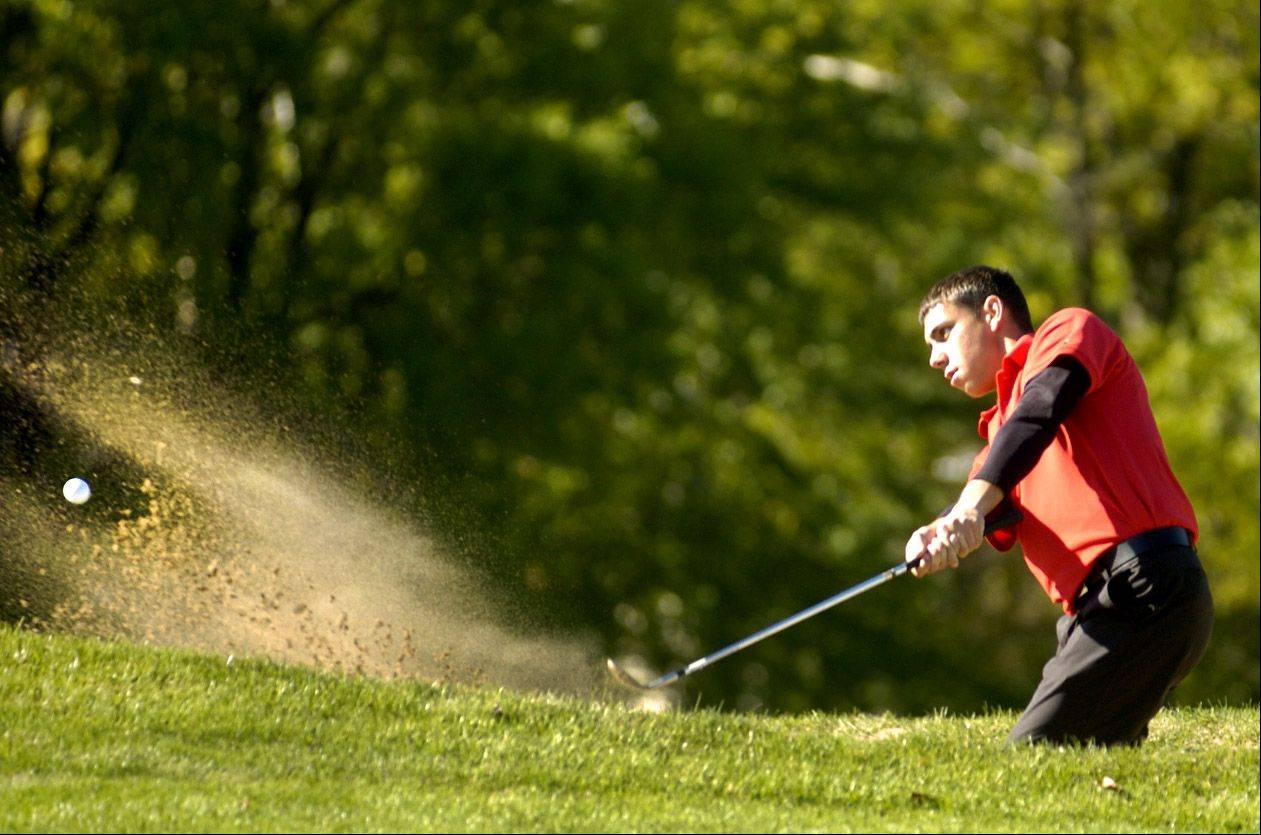 Carmen Valerio of Schaumburg shoots out of the sand on No. 2 during the Mid-Suburban League meet at Arlington Lakes.