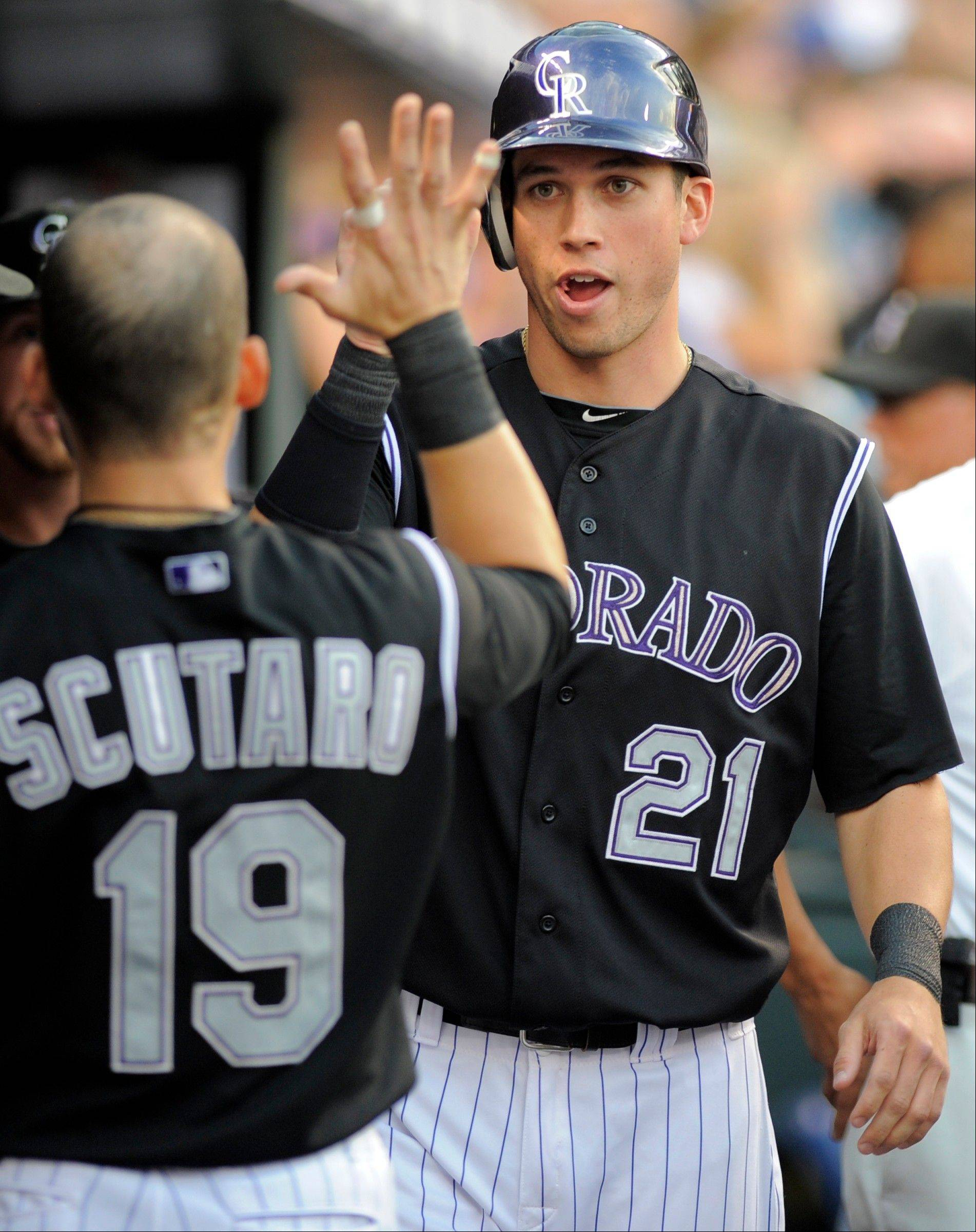 The Rockies' Tyler Colvin is congratulated by Marco Scutaro (19) after scoring a run against the San Diego Padres during the sixth inning of a baseball game in Denver, Friday, June 29, 2012.