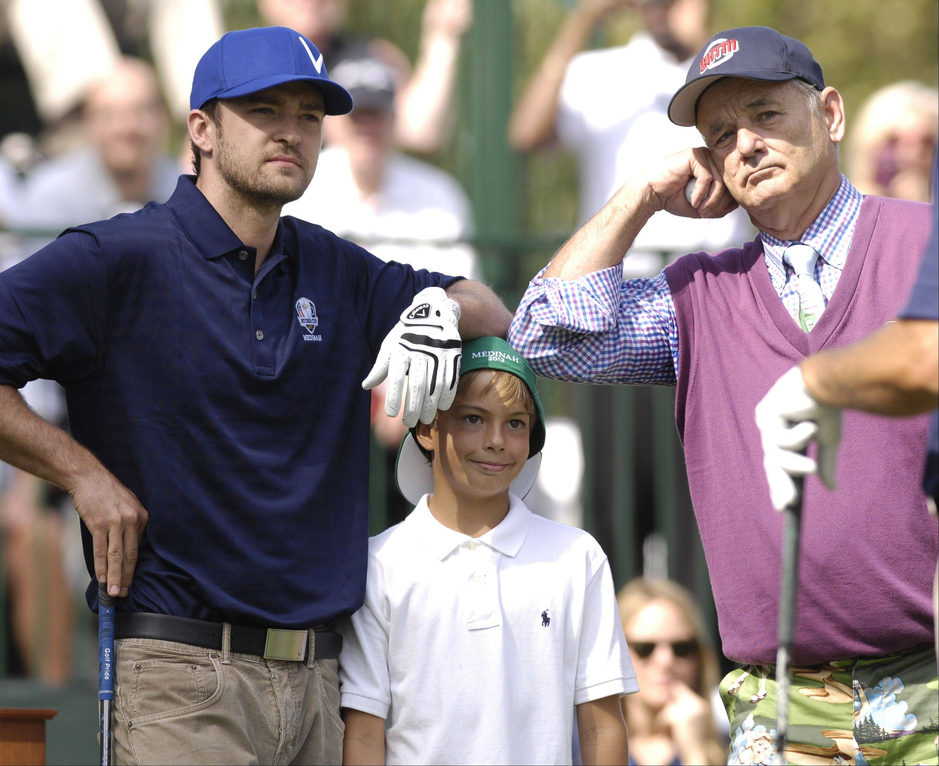 Justin Timberlake and Bill Murray have some fun with a young golf fan before teeing off.