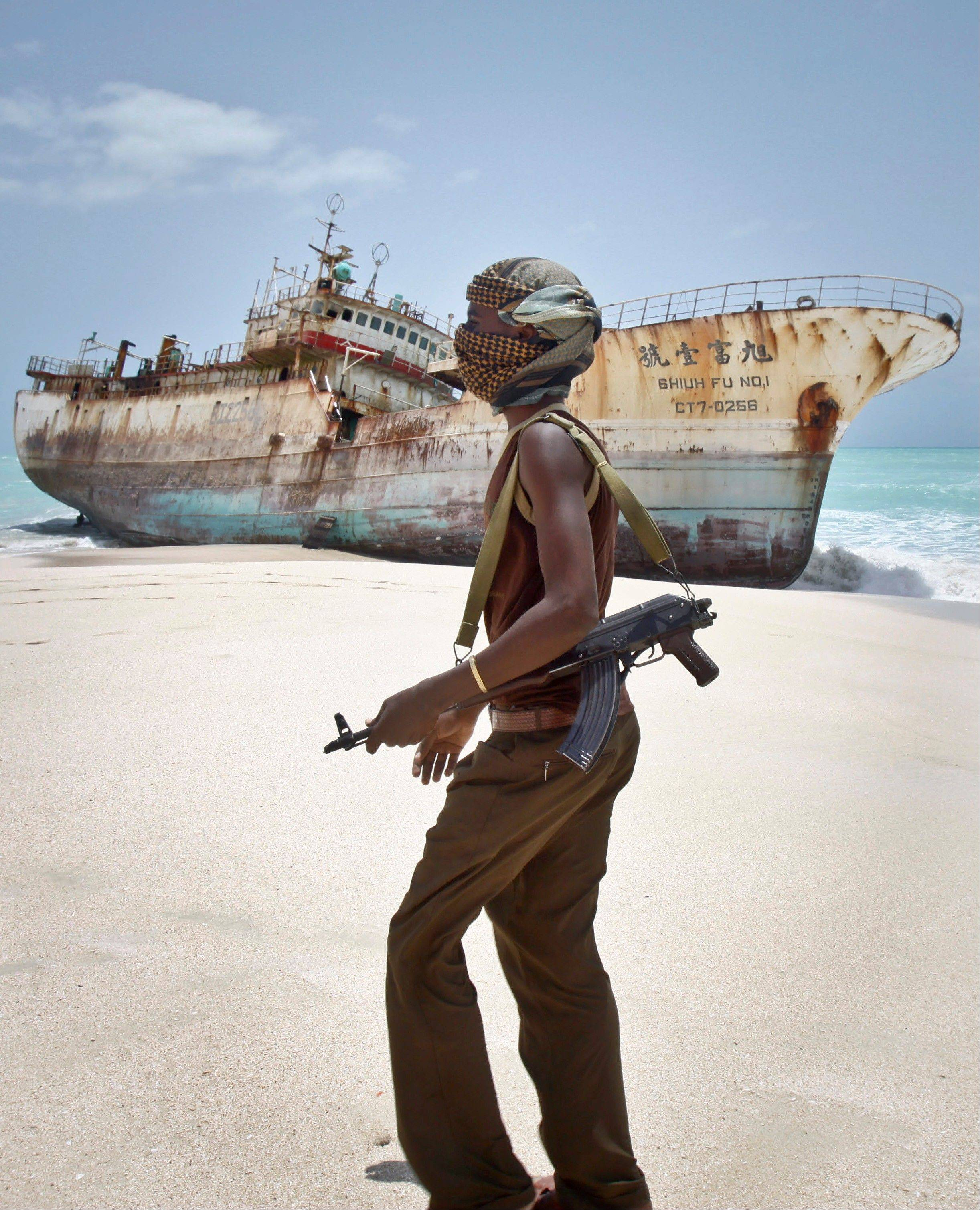 In this photo taken Sunday, masked Somali pirate Abdi Ali walks past a Taiwanese fishing vessel that washed up on shore after the pirates were paid a ransom and released the crew, in the once-bustling pirate den of Hobyo, Somalia.