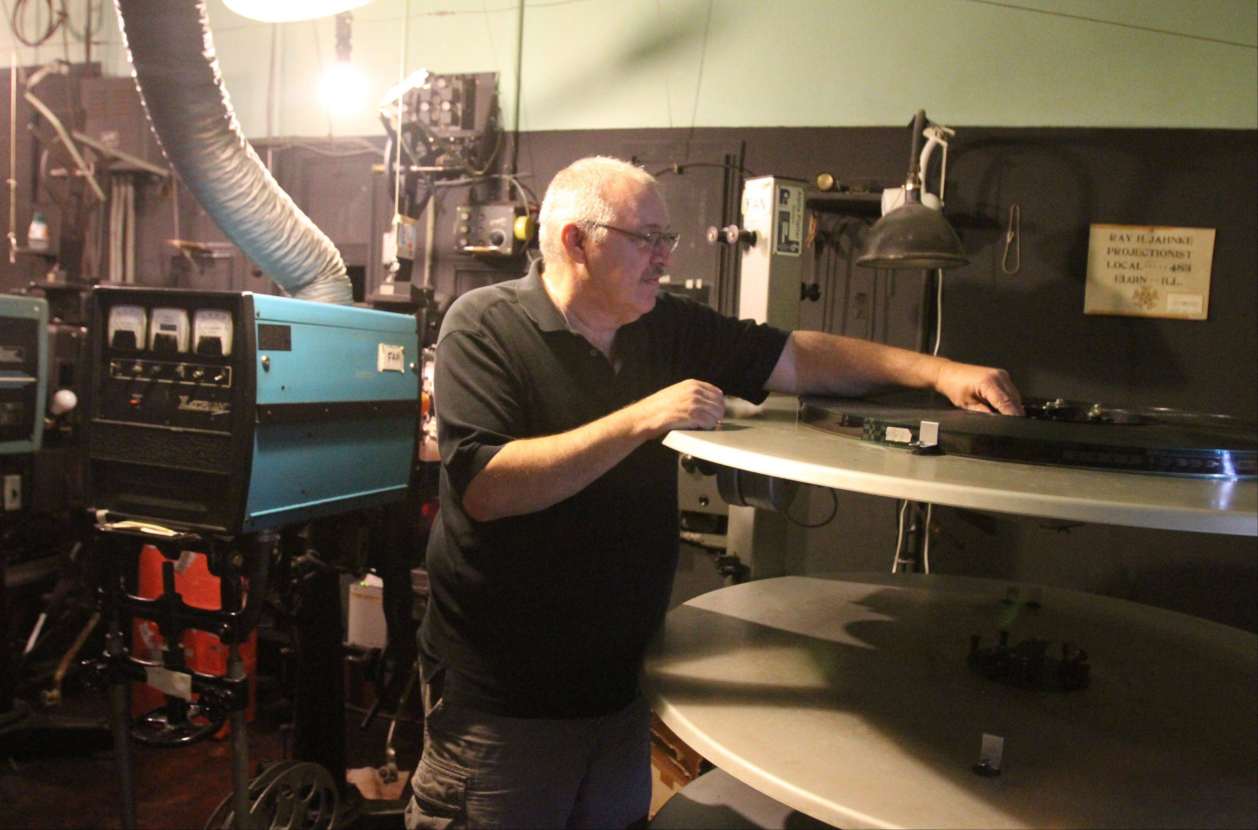 Catlow theater co-owner Tim O'Connor demonstrates how movie film is currently loaded onto a giant reel table that is then fed into the mid-20th century Simplex XL film projector at the theater in Barrington. O'Connor said that allows the film projector operator to show the film as one piece versus holding a new reel one-third of the way through a movie.