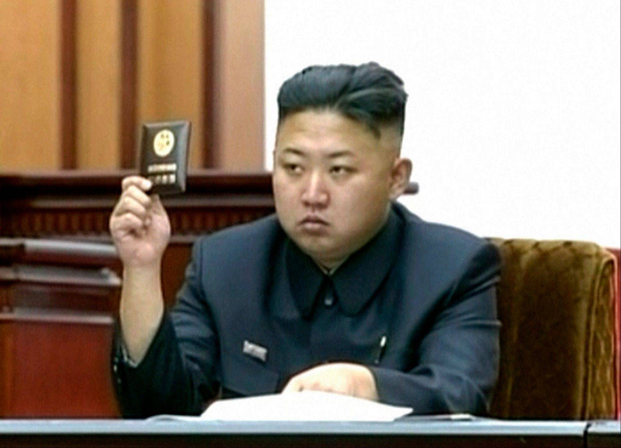 In this video image taken from KRT, North Korean leader Kim Jong Un holds up his credential at the Supreme People's Assembly's second meeting of the year, in Pyongyang, North Korea, Tuesday, Sept. 25, 2012. North Korea's parliament convened Tuesday for the second time in six months, passing a law that adds one year of compulsory education for children in the socialist nation, the first publicly-announced policy change under leader Kim.