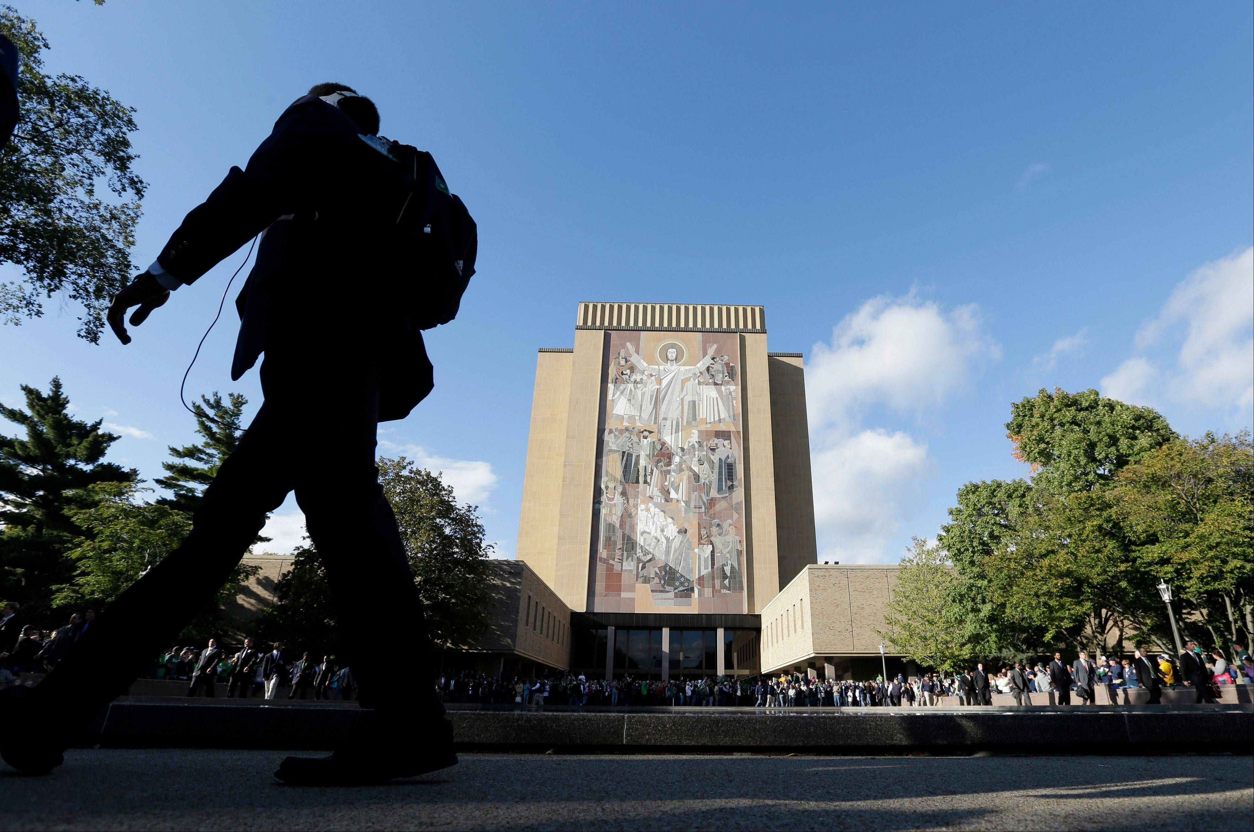 "A Notre Dame defensive player walks past ""Touchdown Jesus"" as he arrives Saturday for the game against Michigan Saturday."