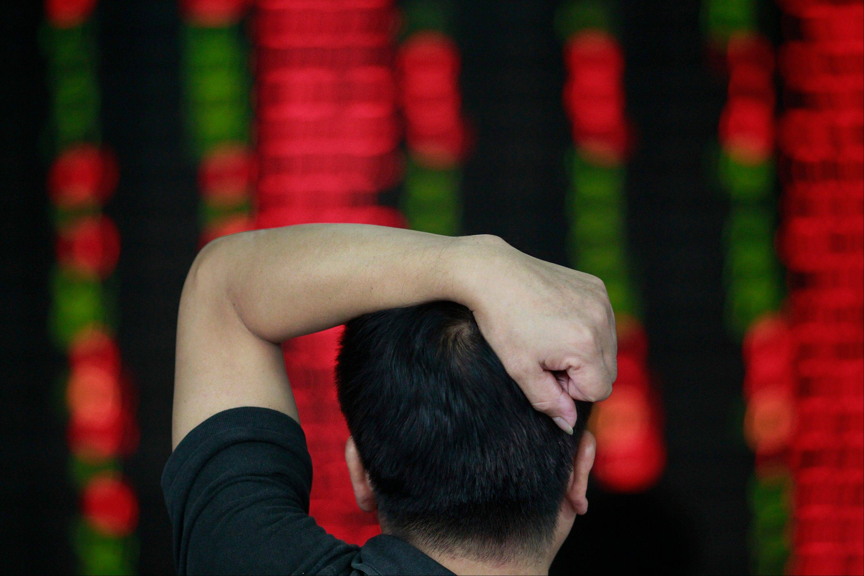 An investor looks at the stock price monitor at a private securities company in Shanghai, China, Tuesday.