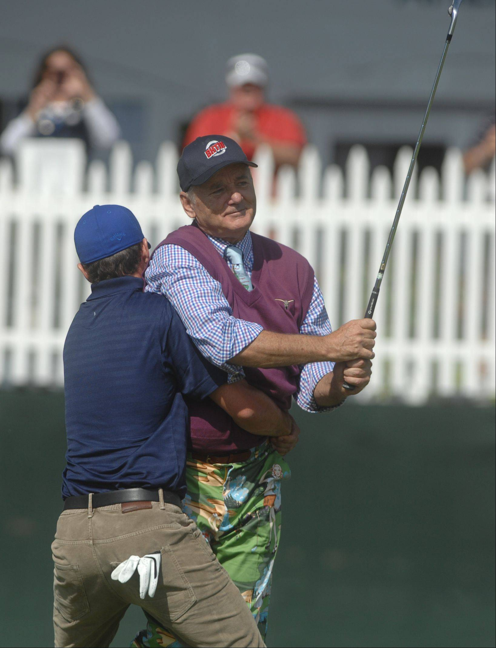 Justin Timberlake lifts Bill Murray up after a putt on the second hole at Medinah Country Club on Tuesday.